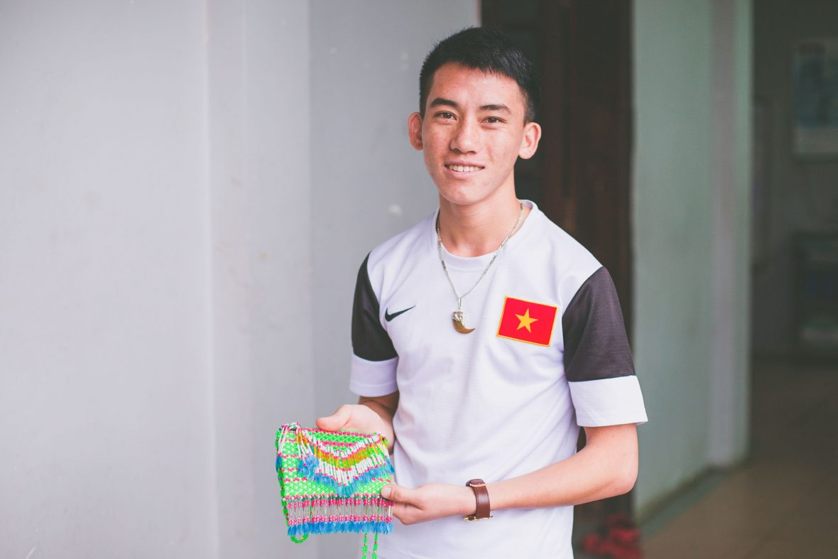 Class 34 trainee, 18-year-old Do, holds a traditional Hmong beaded bag made for him by his sister.