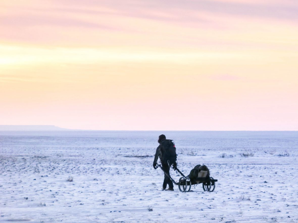 Fellow adventurer Rob Lilwall drags the cart through the snowy wastes of the Gobi Desert.