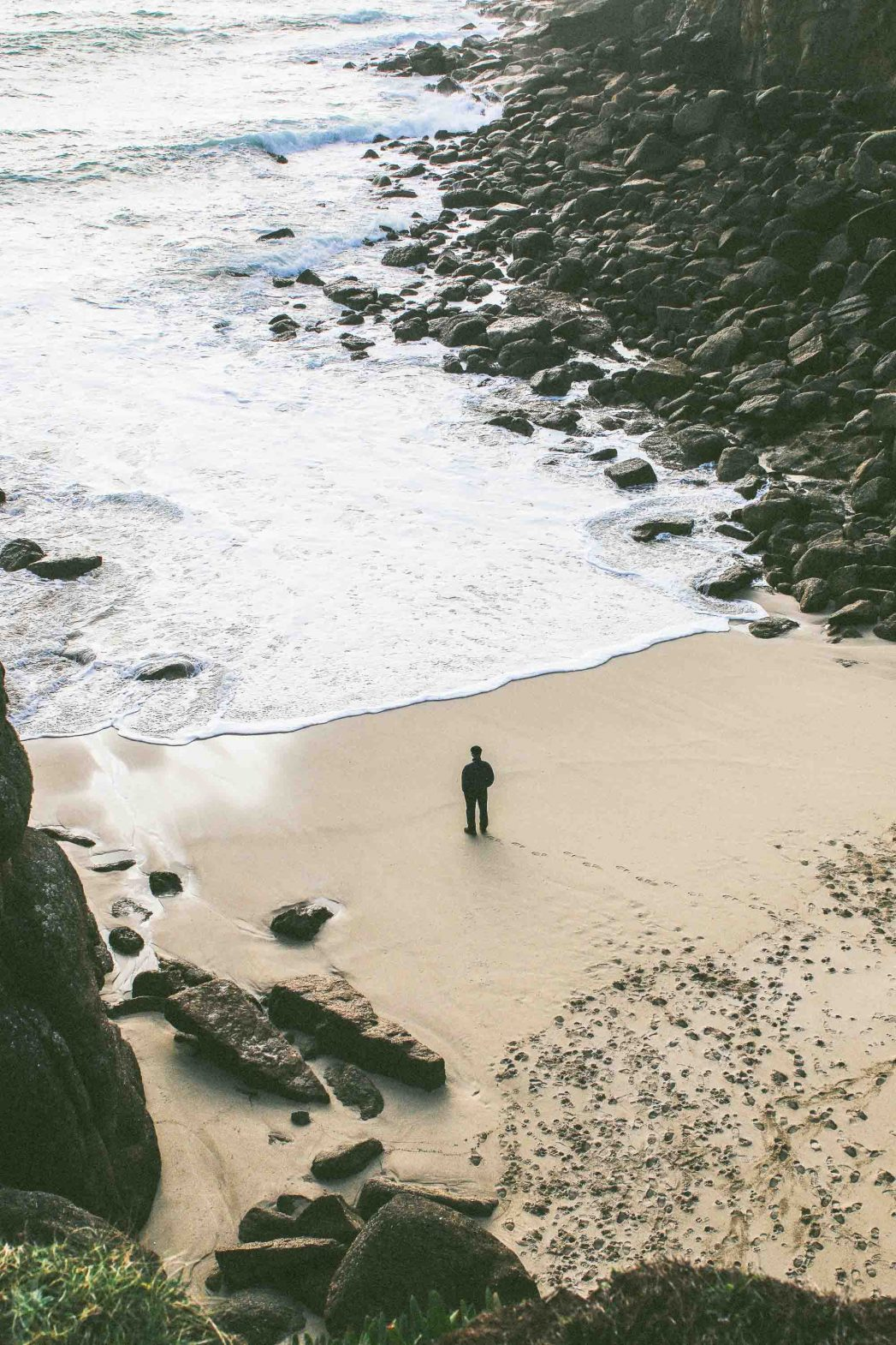 A solitary figure on a beach in Cornwall.