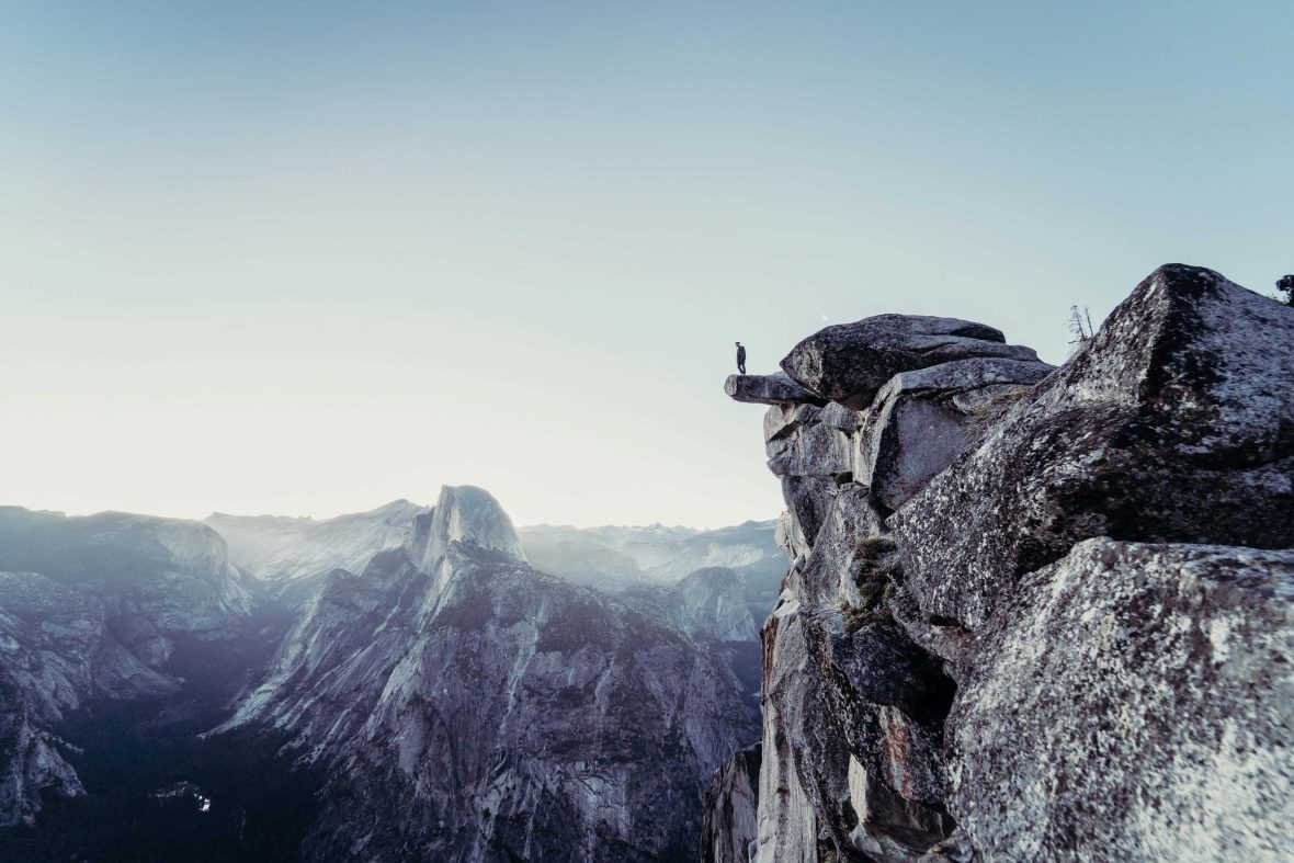 A man looks over the edge of a cliff in the spectacular Yosemite National Park, USA.