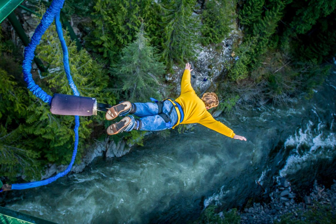 A man overcomes the fear to bungee-jump high above a rushing river.