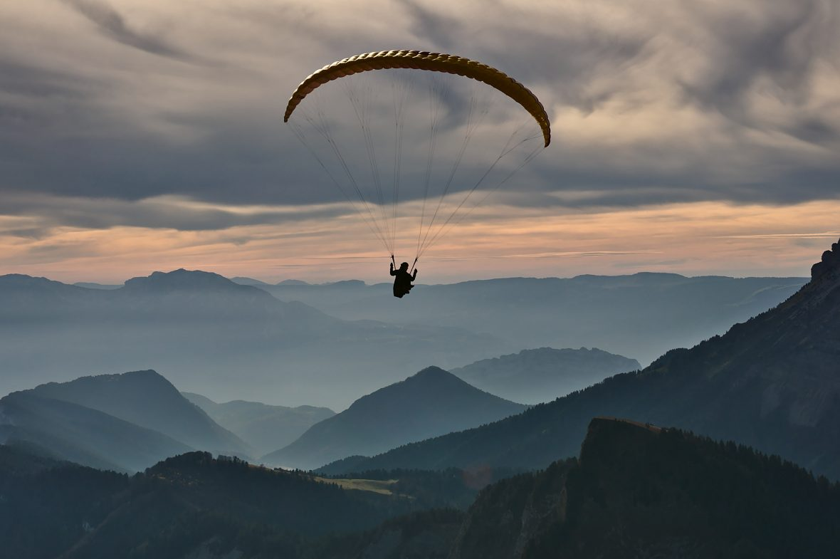 A paraglider flies high above the mountains as dusk sets in.