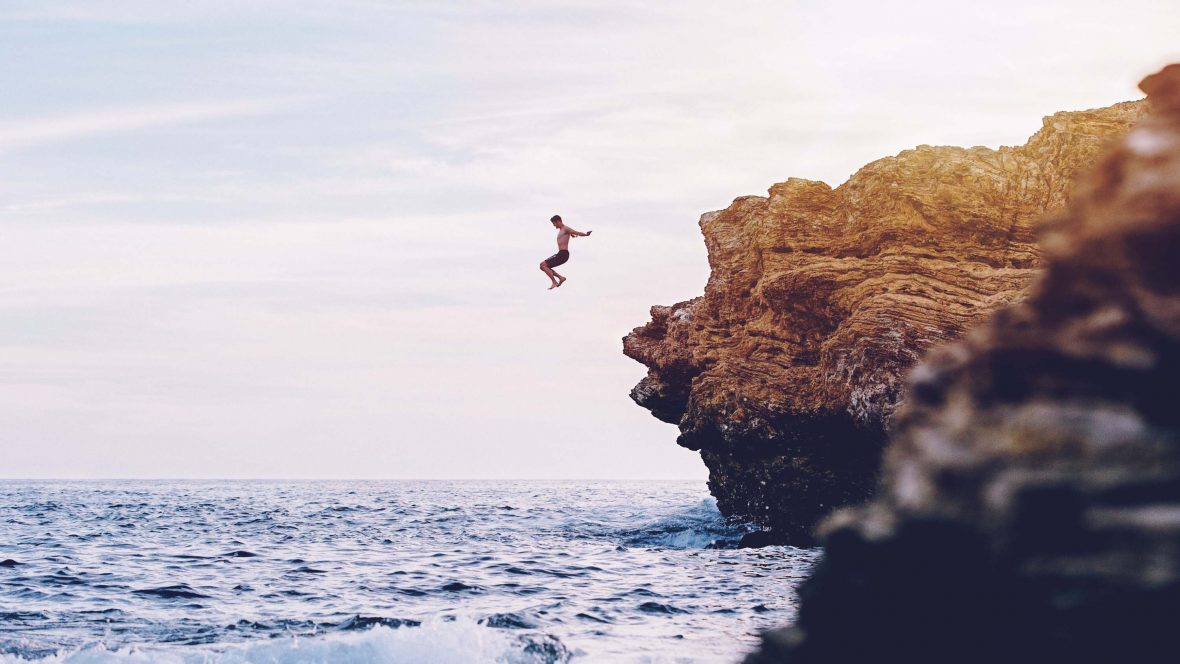 A man jumps from the rocks at Newport beach, California, USA.