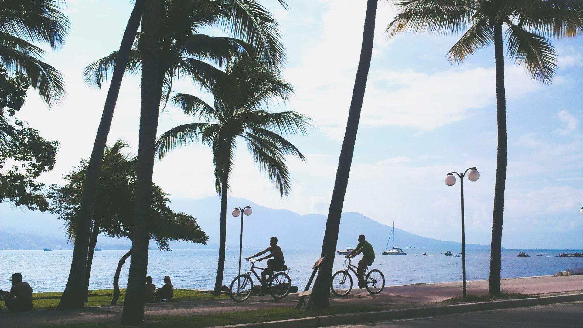 People ride along the boulevard in Ilhabela, Brazil.