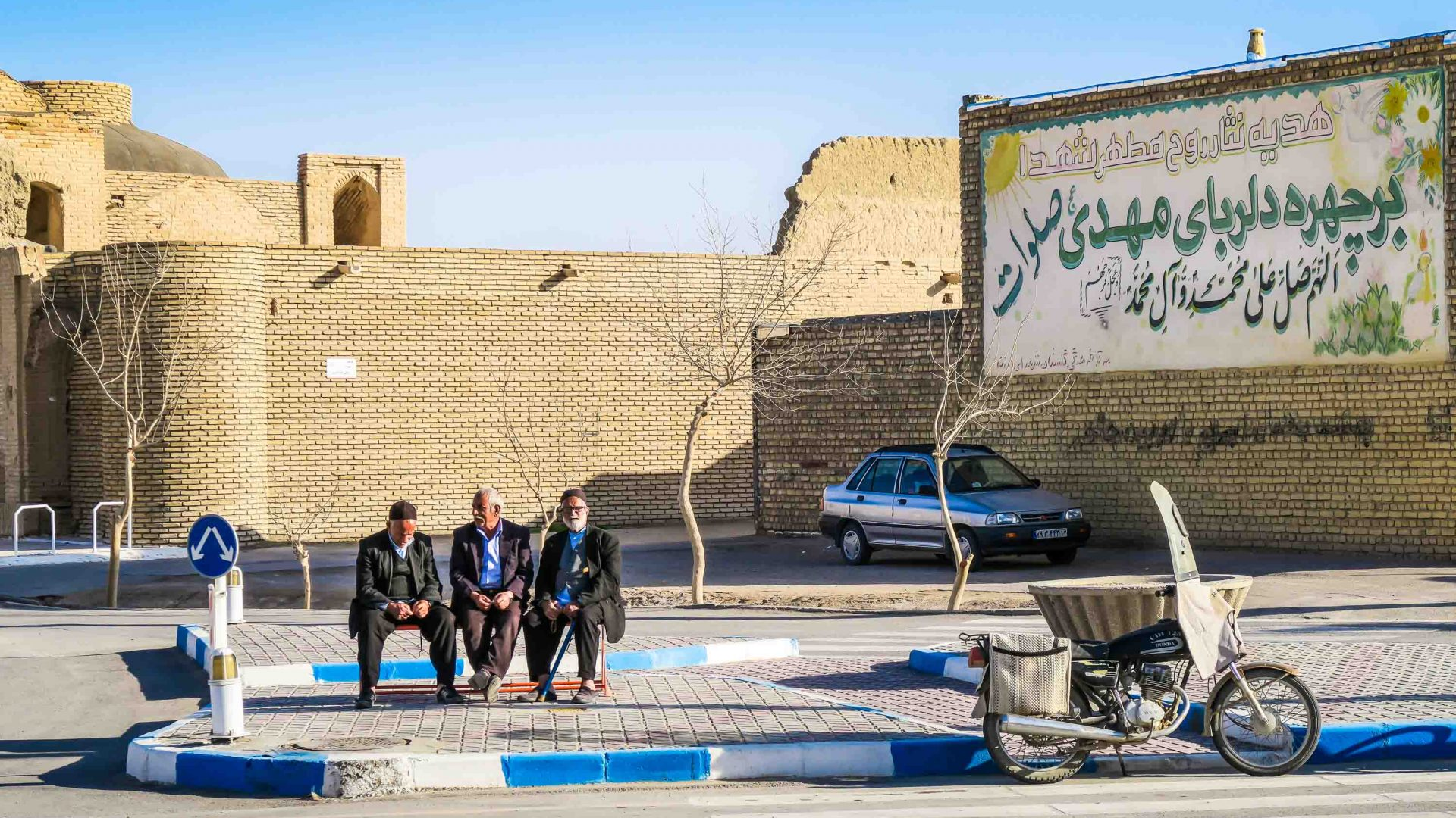 Locals sit in the street in Varzaneh.
