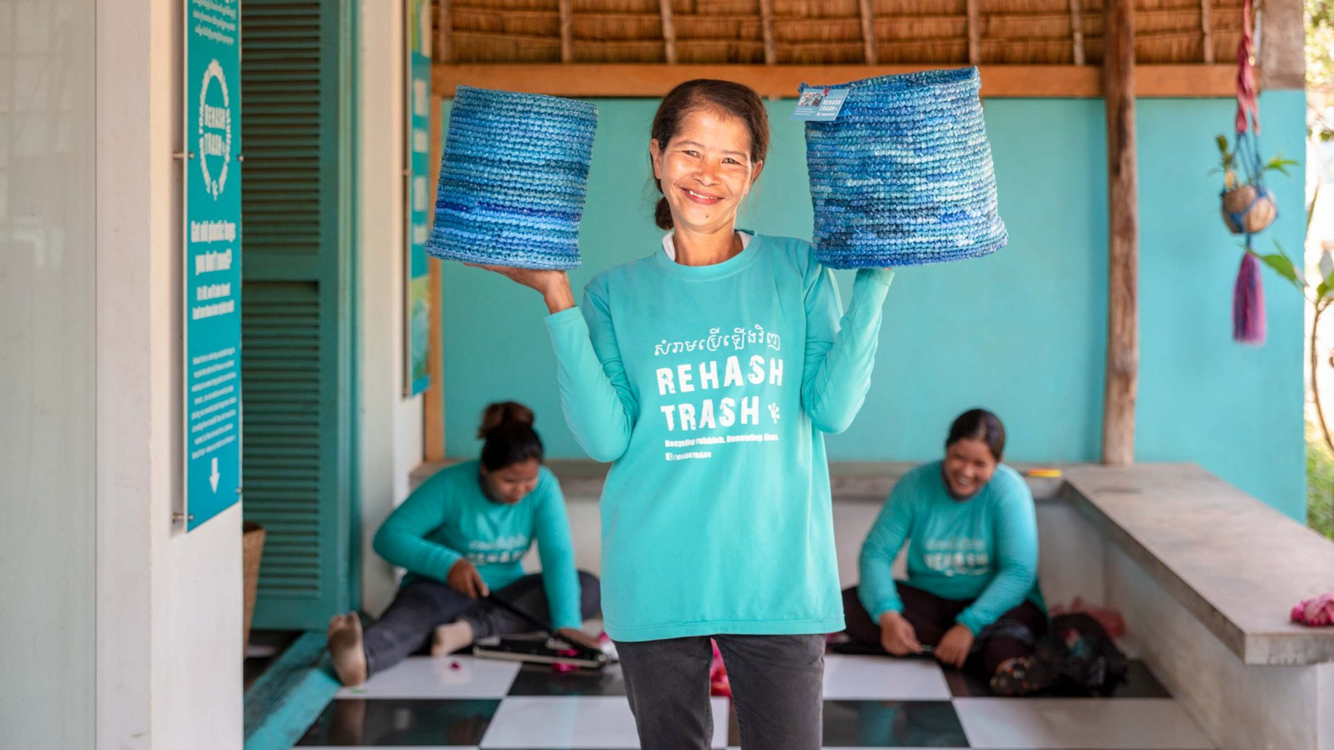 A women from the Cambodian organization Rehash Trash shows off some of the baskets she has made.