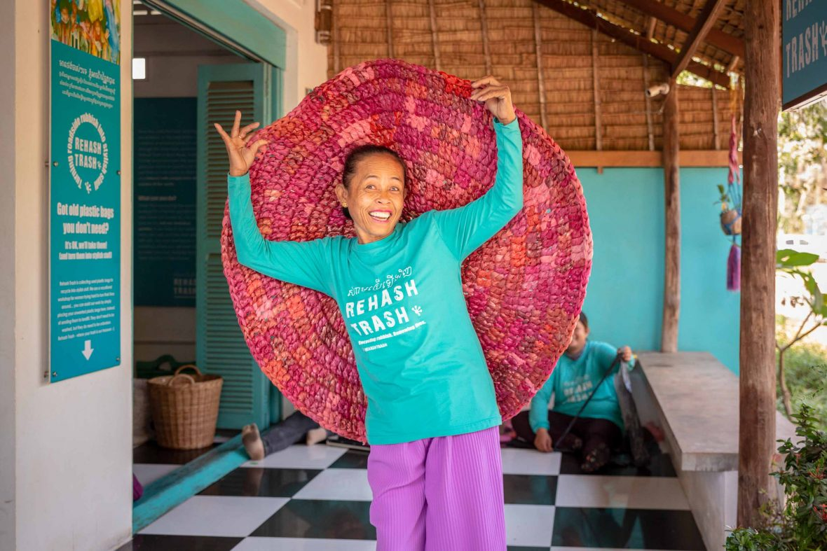One of the women from the Cambodian organisation Rehash Trash shows off one of the mats she has made.