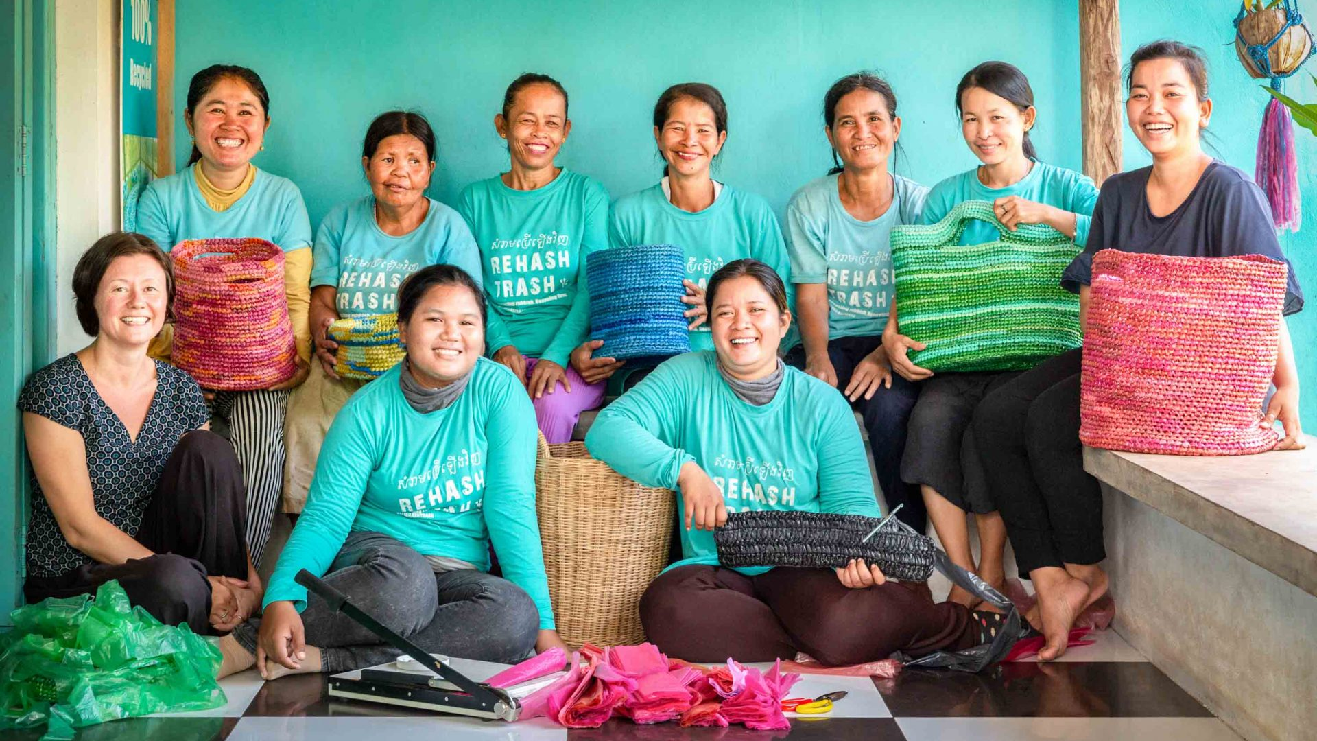 Women who work at Rehash Trash in Cambodia pose for a photo along with some of their creations, made using plastic bags found on the streets.