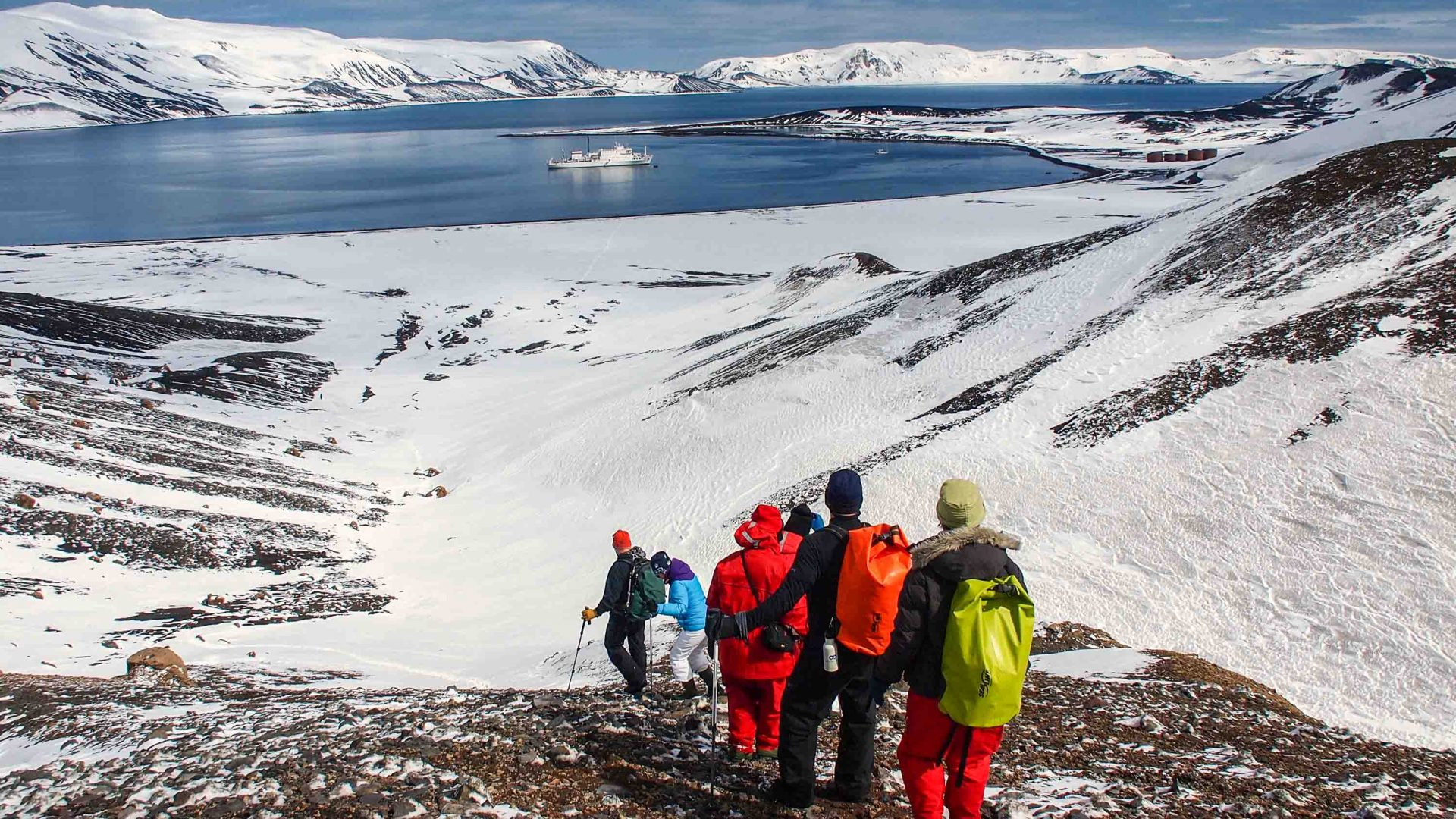 A group walks along Deception Island in Antarctica.