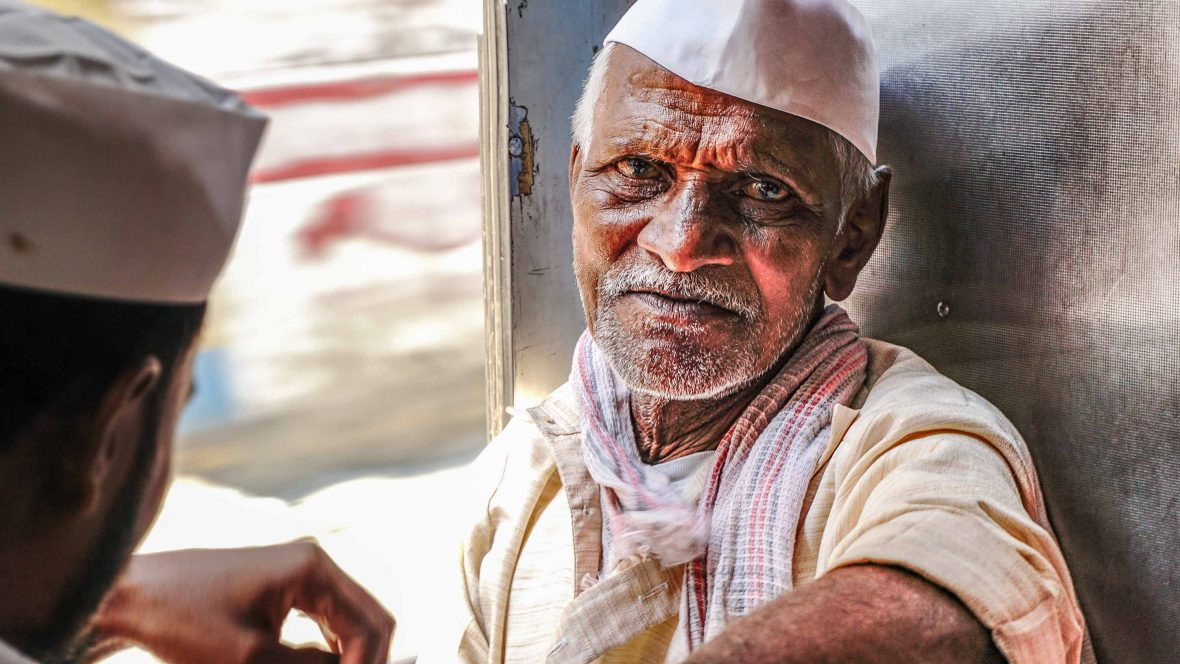 An 80-year-old Dabbawala on the train, delivering the orders for the day.