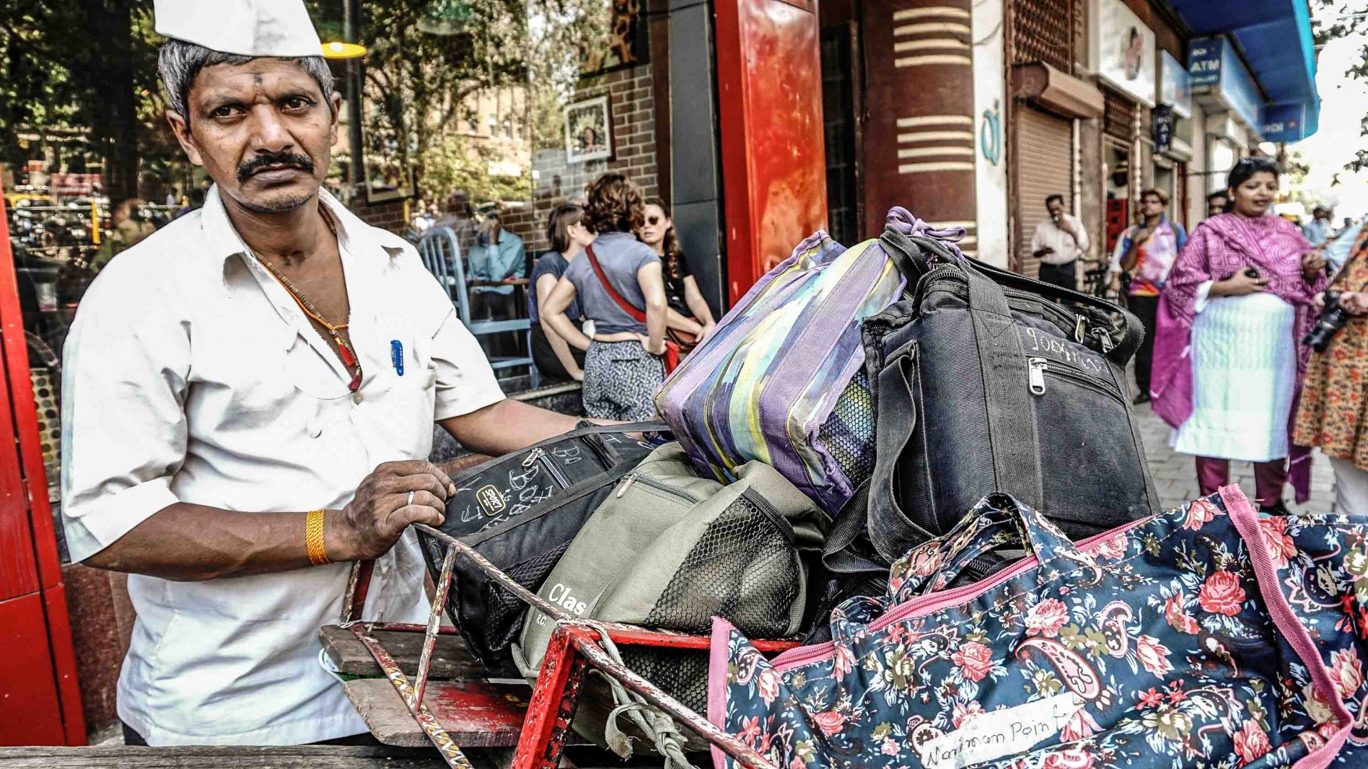 A dabbawala pushes his lunch load through Churchgate after getting off the train.