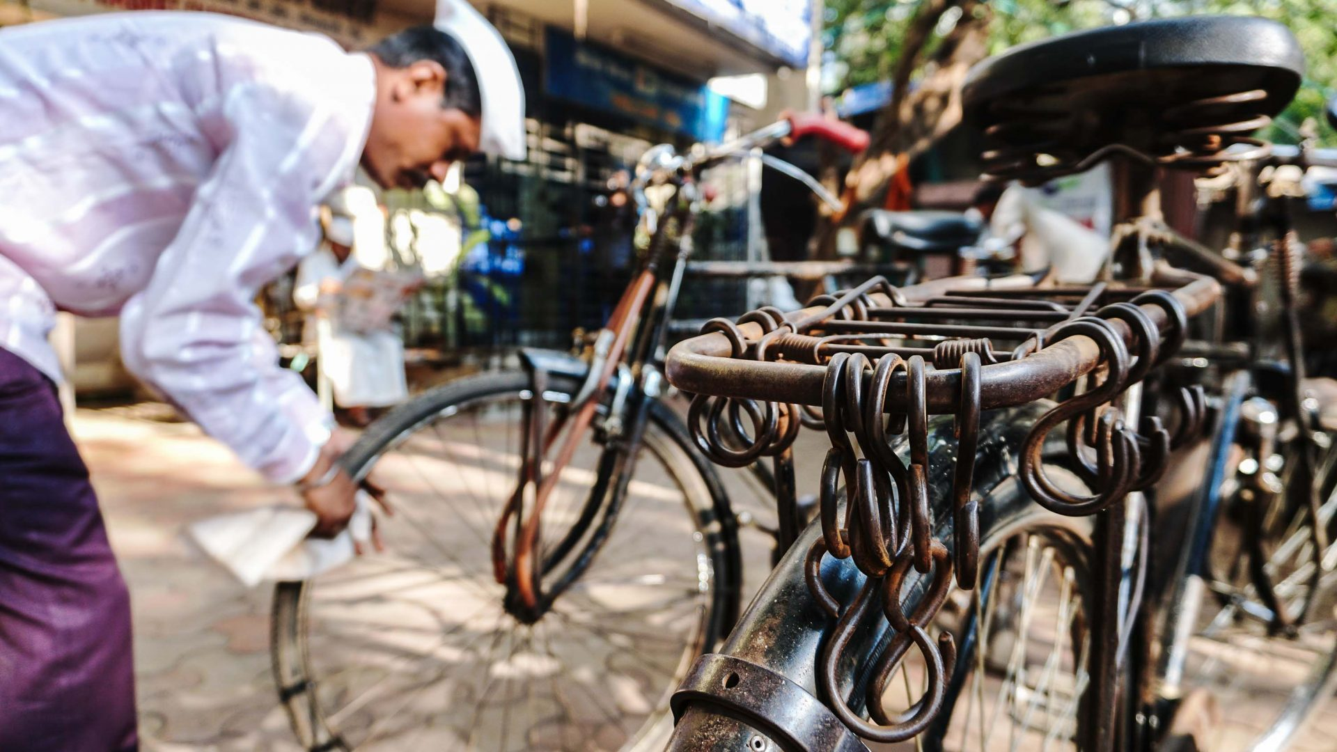 A dabbawala prepares his bicycle so that it's ready to carry the day's orders.