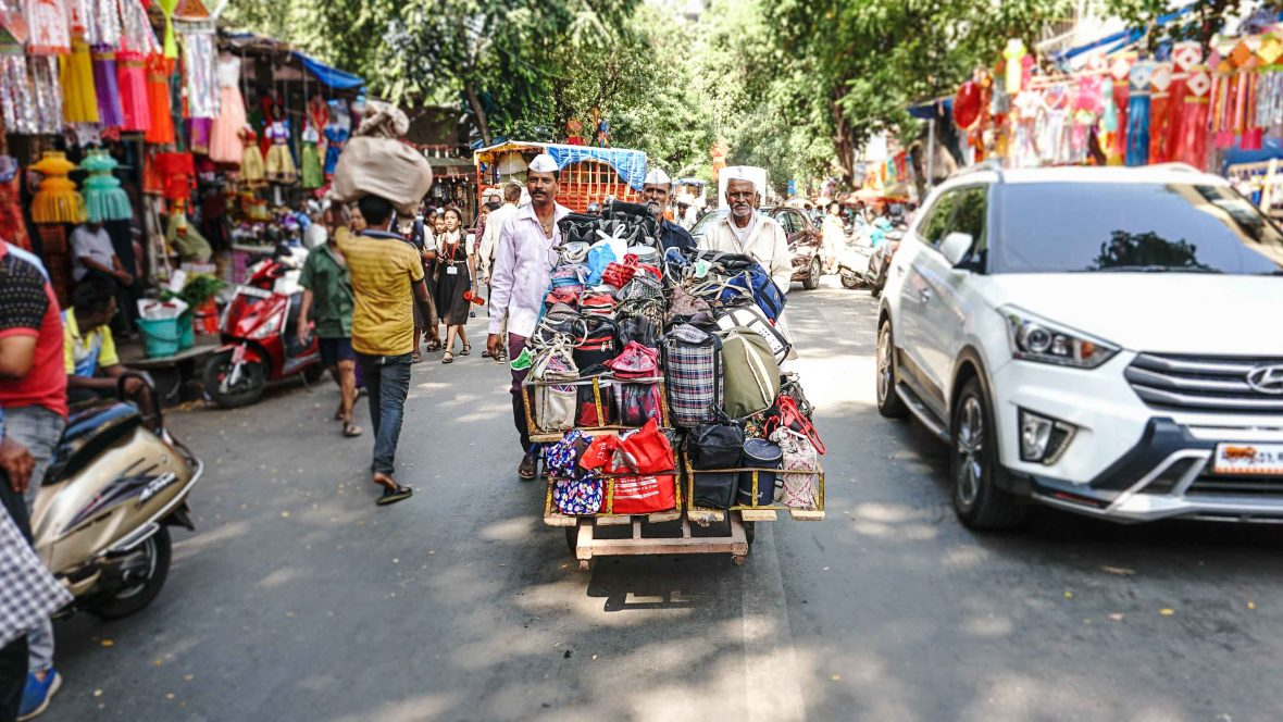 Dabbawalas pull a handcart piled high with lunch orders through the streets.