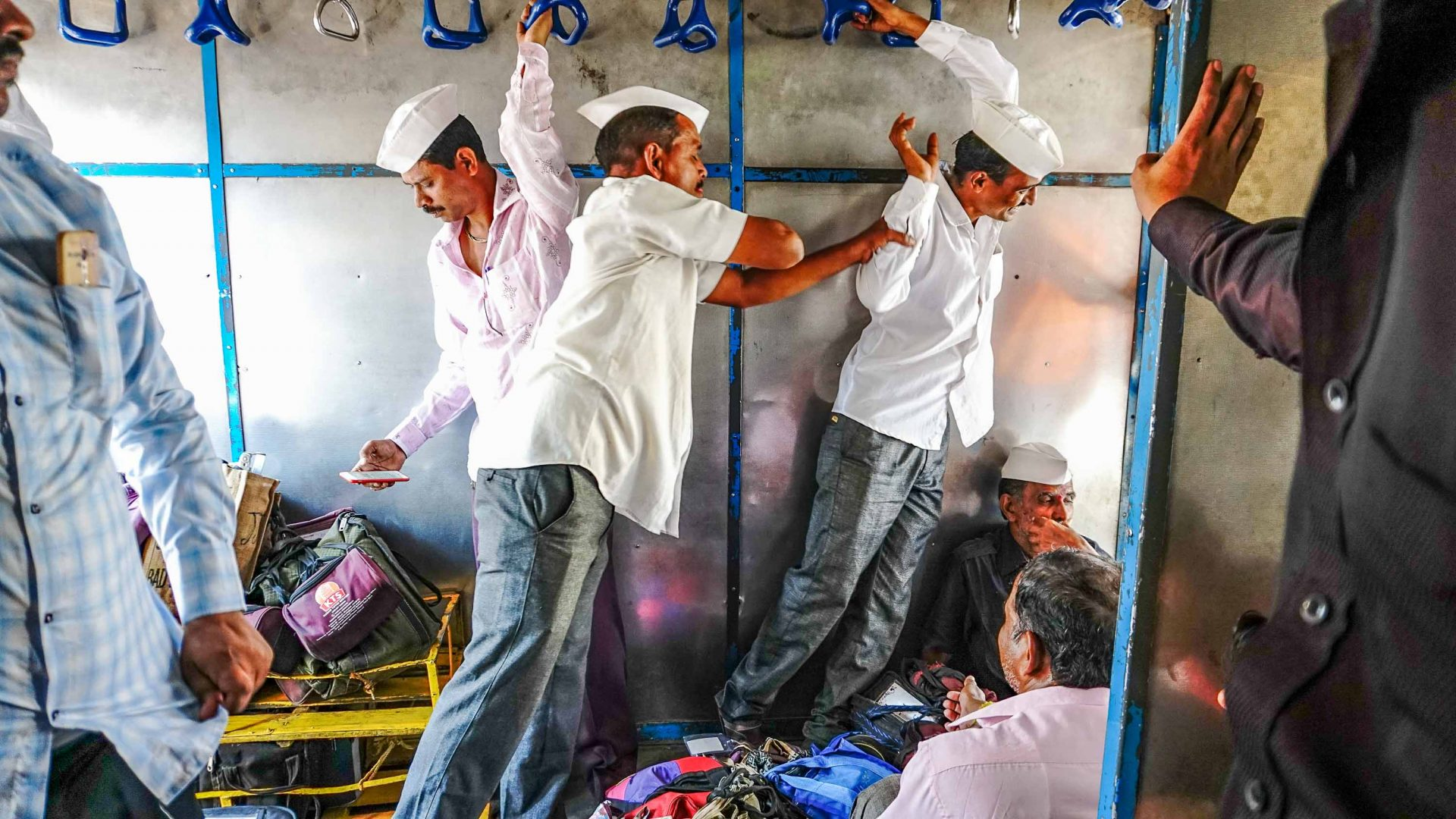Once aboard the train, the dabbawalas relax and engage in playful banter.