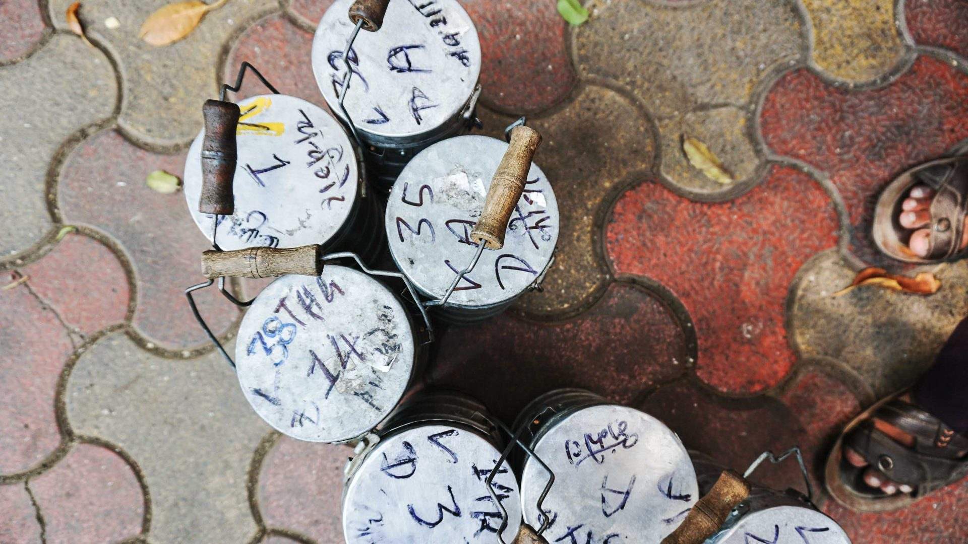 Tiffins carrying lunch are marked with a complex system of codes indicating a pick-up point, drop-off, train station, and the individual dabbawala responsible for its journey.
