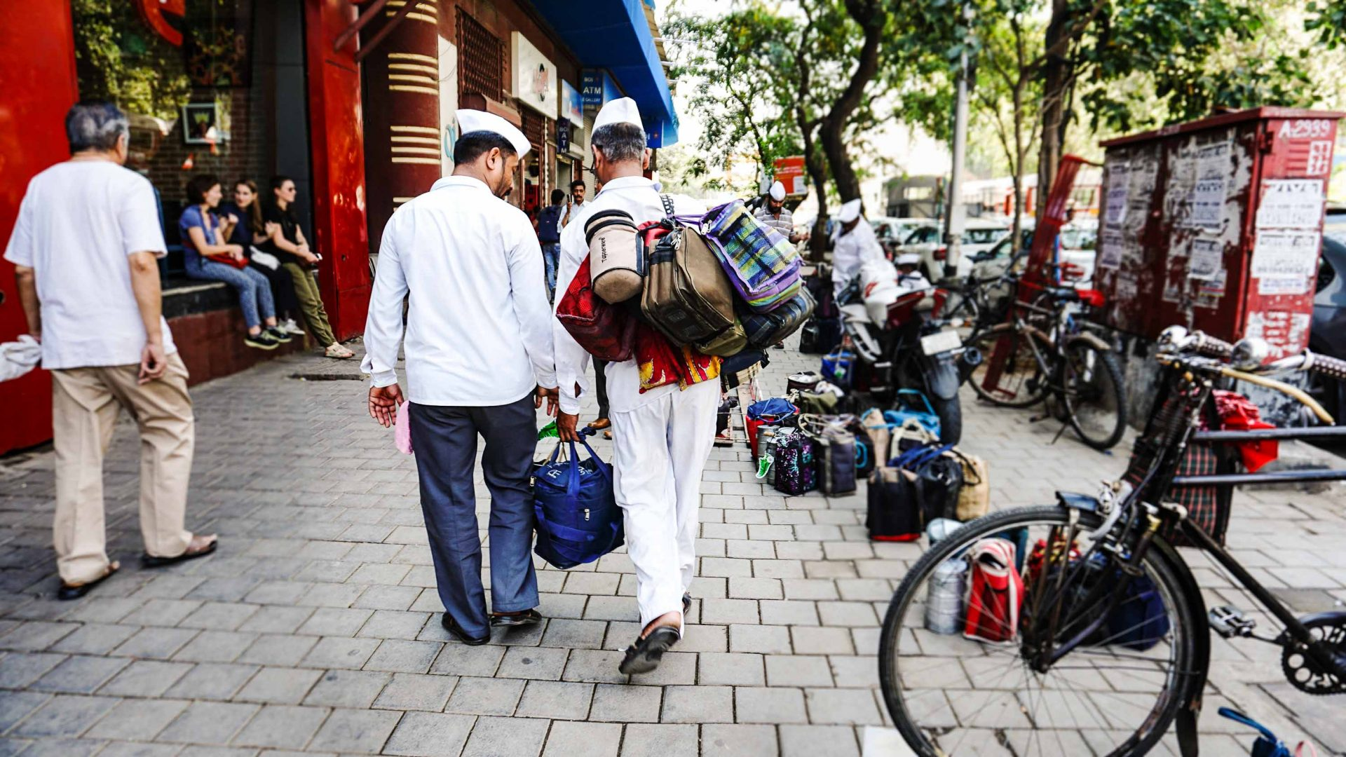 Dabbawalas laden with lunchboxes and tiffins walk through central Mumbai.