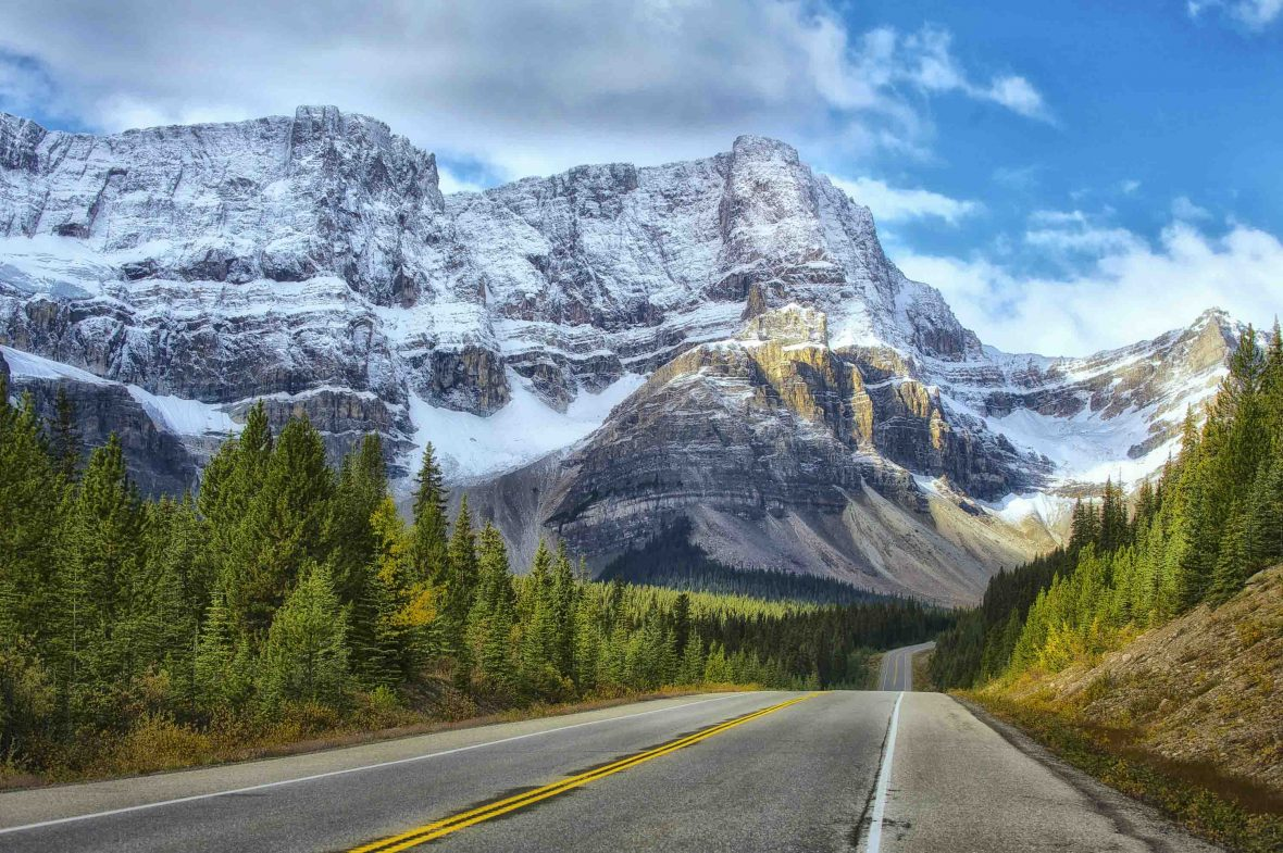 The road winds through Banff, Canada.