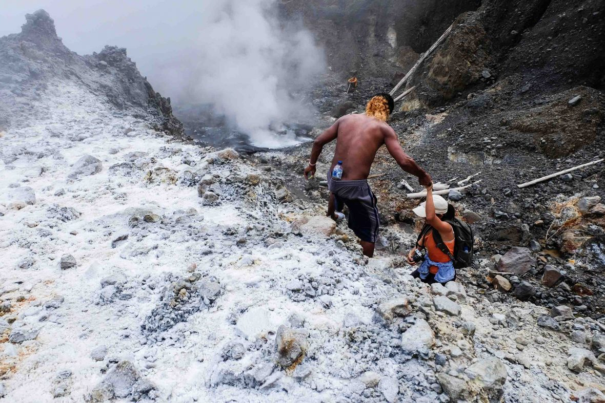 People climb up the walls of the ever-steamy Colo volcano.