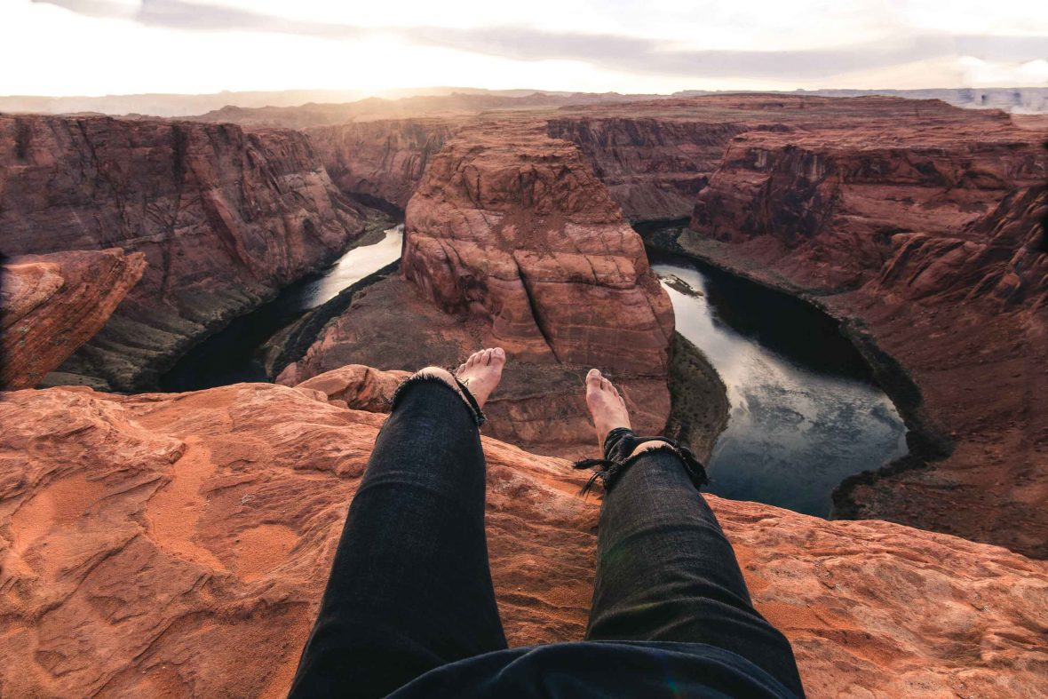 A traveler dangles their legs from the ledge at Horseshoe Bend National Park in the USA.