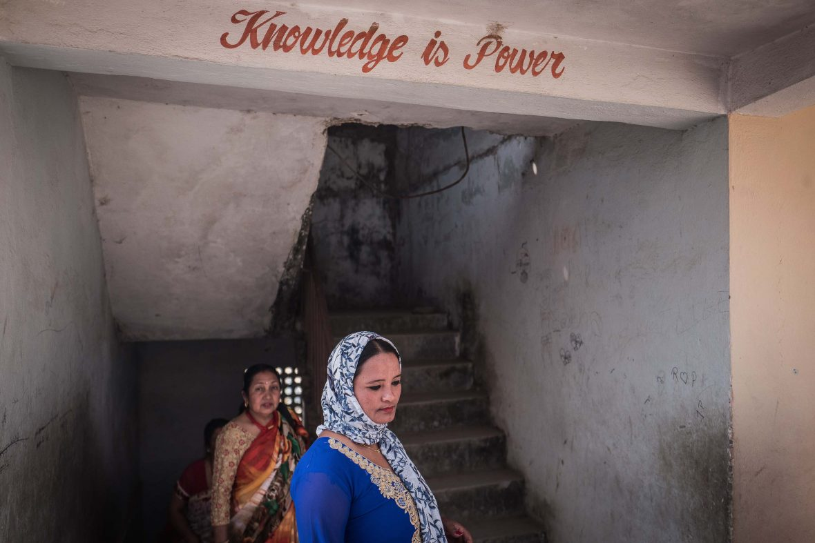 Women gather at a school hall with a sign above them that aptly reads 'knowledge is power'.