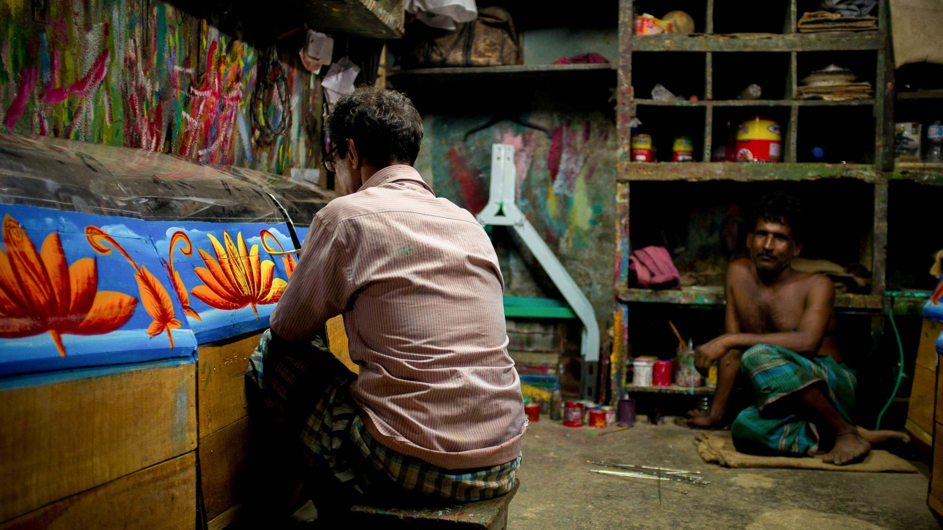 Bonjo painting a lily at his workshop in Chittagong, Bangladesh.
