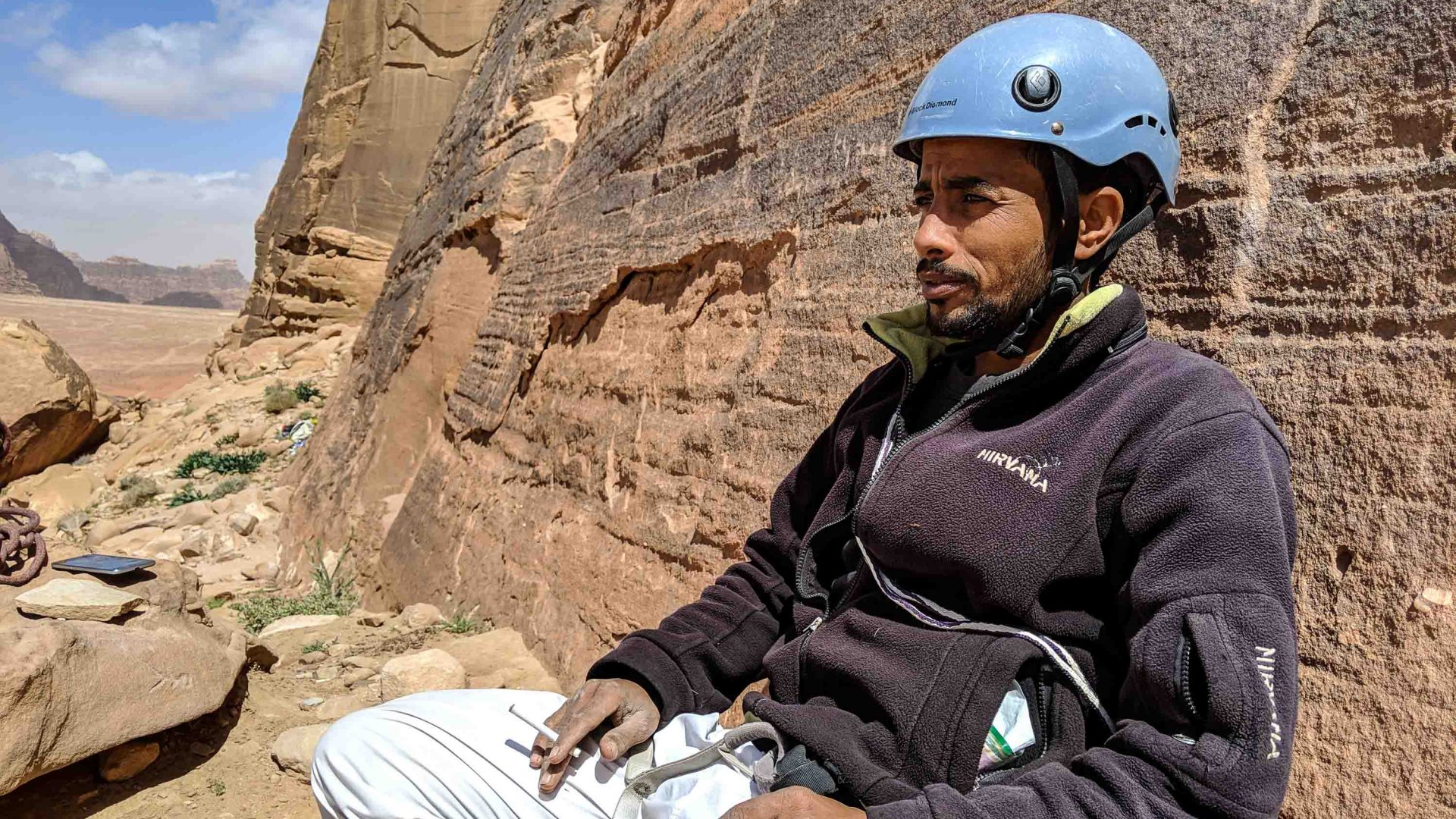 Abdullah from the locally run Shabab Sahra guide association smokes a cigarette at the base of the rock face.