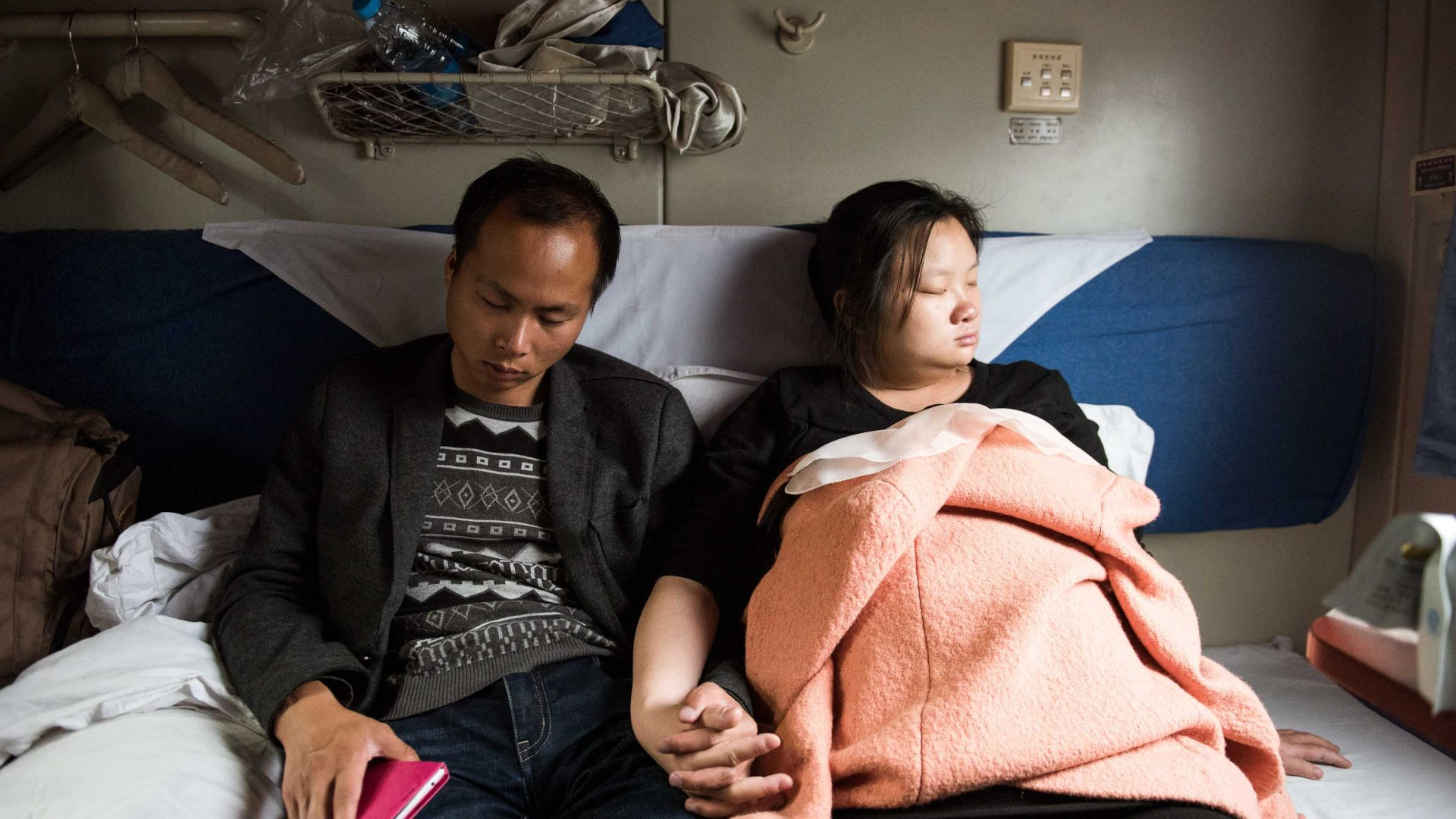 A couple sleep hand-in-hand during a train journey.