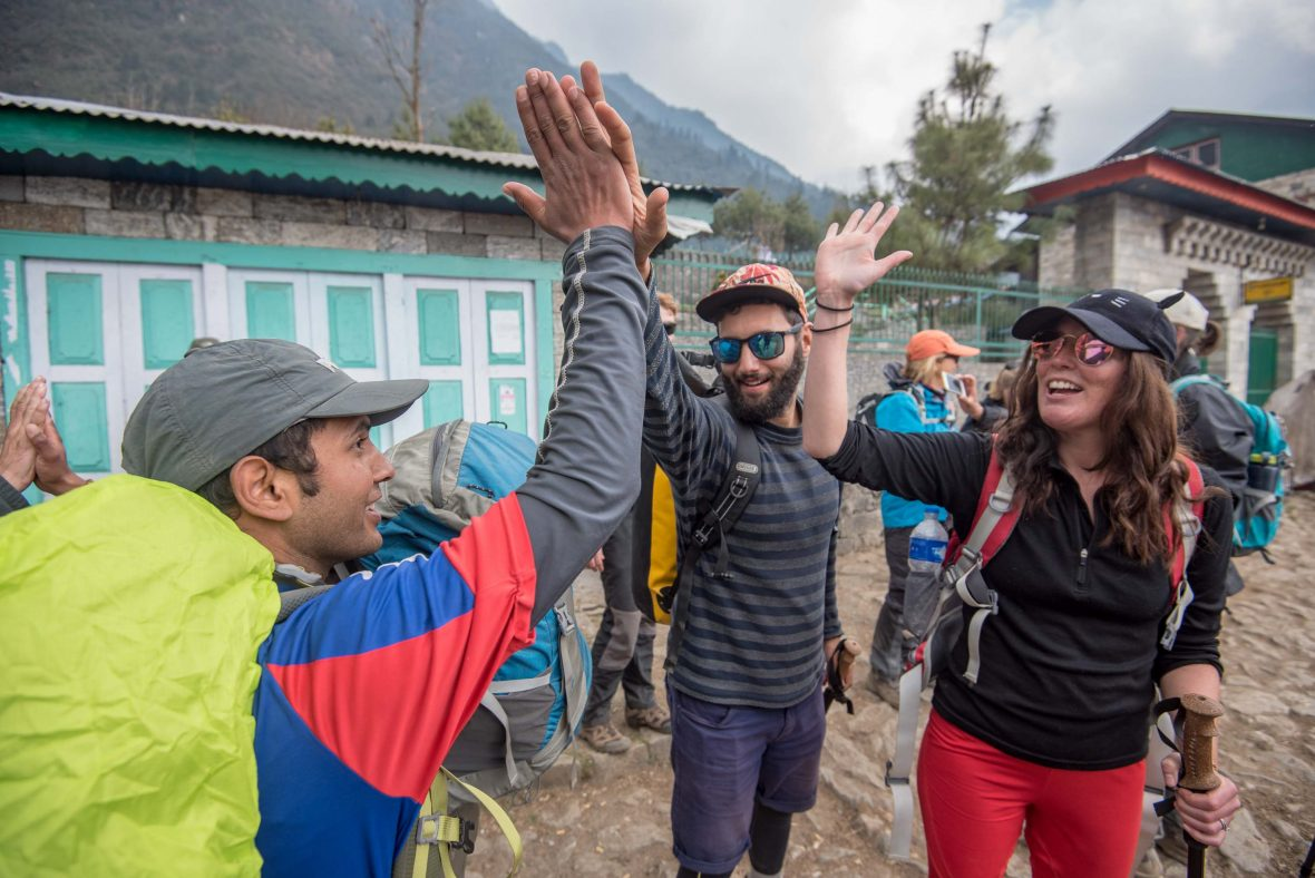 Travelers high-five their guide in Lukla, Nepal, during the Everest Base Camp trek.