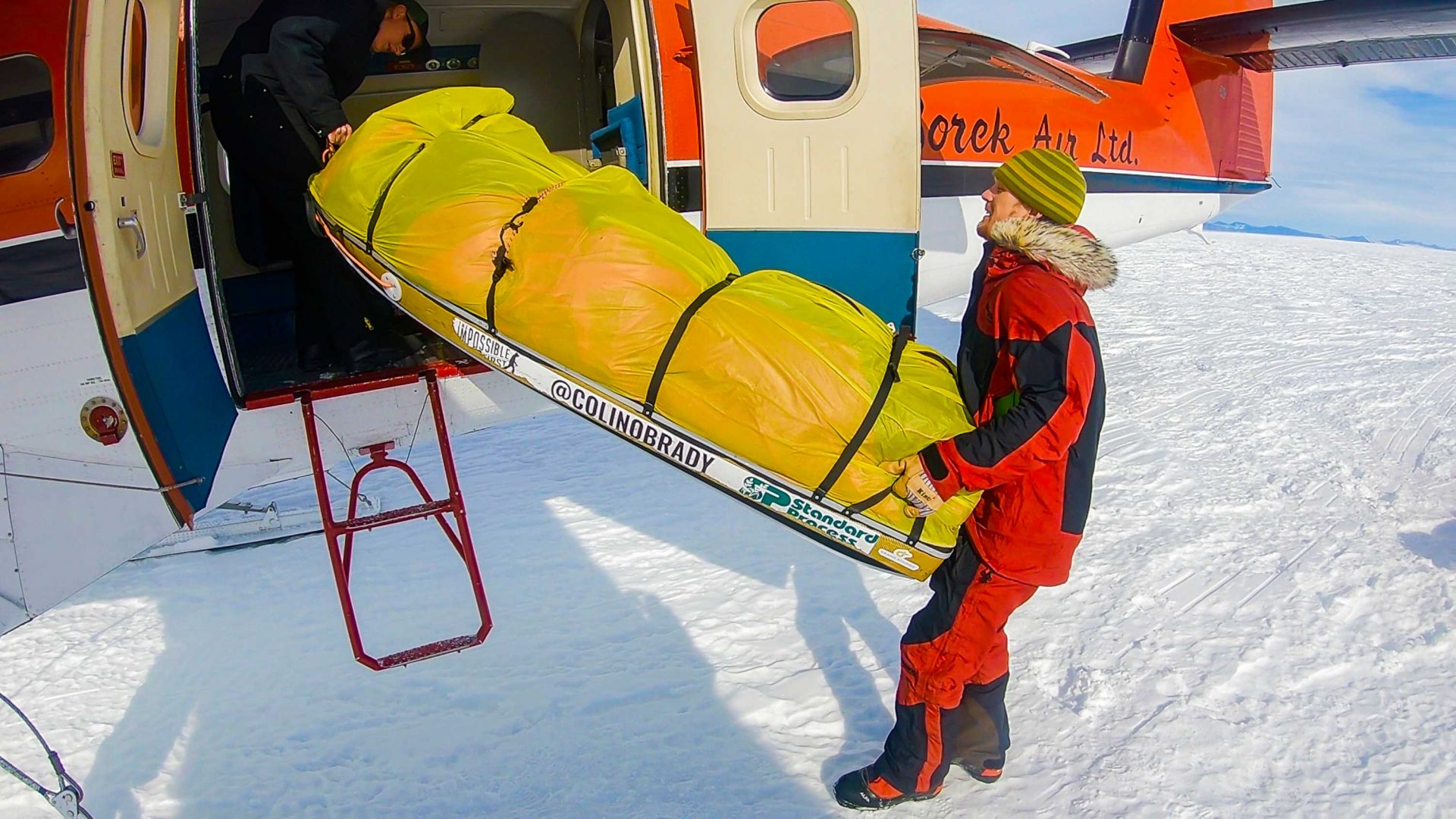 Colin O'Brady lifts his sled into the helicopter upon completing his unsupported journey through Antarctica.
