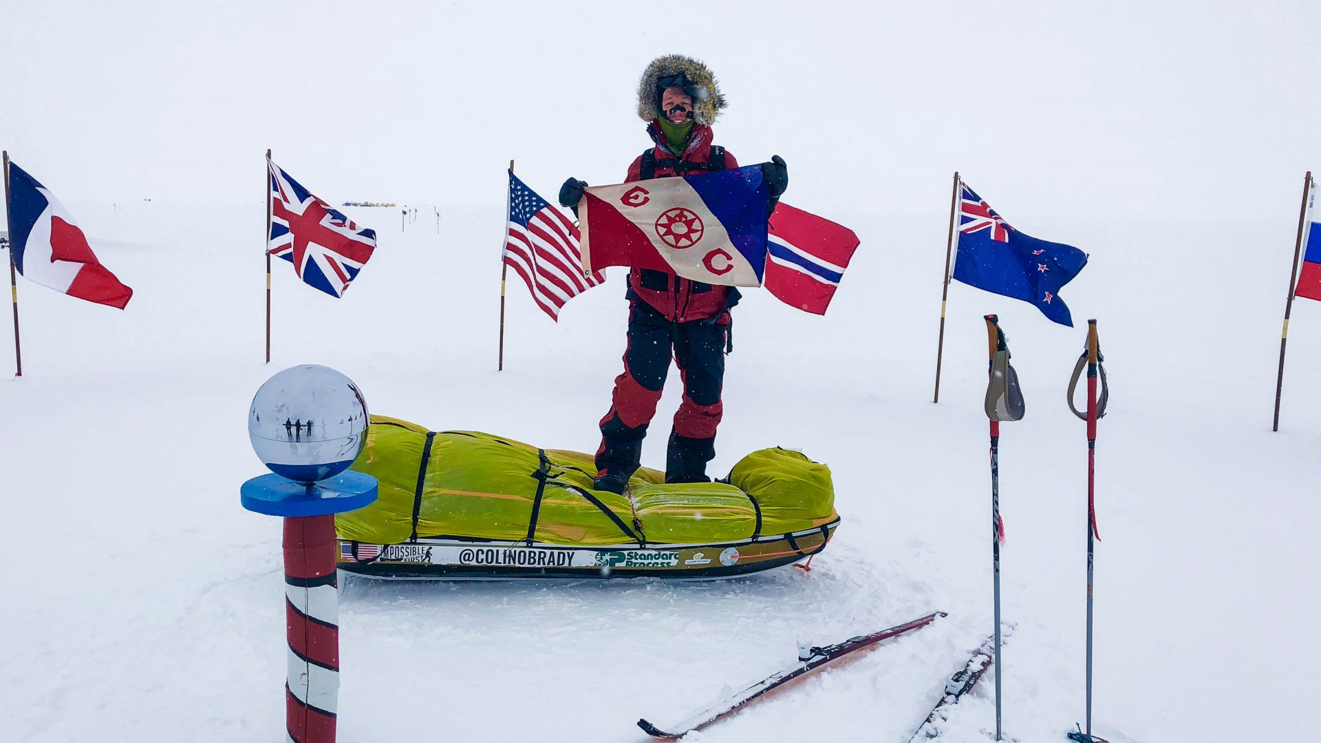 Colin O'Brady surrounded by flags from other countries which have also been through Antarctica.