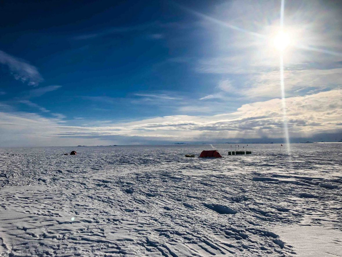 Colin O'Brady';s tent, barely visible in the snow of Antarctica.