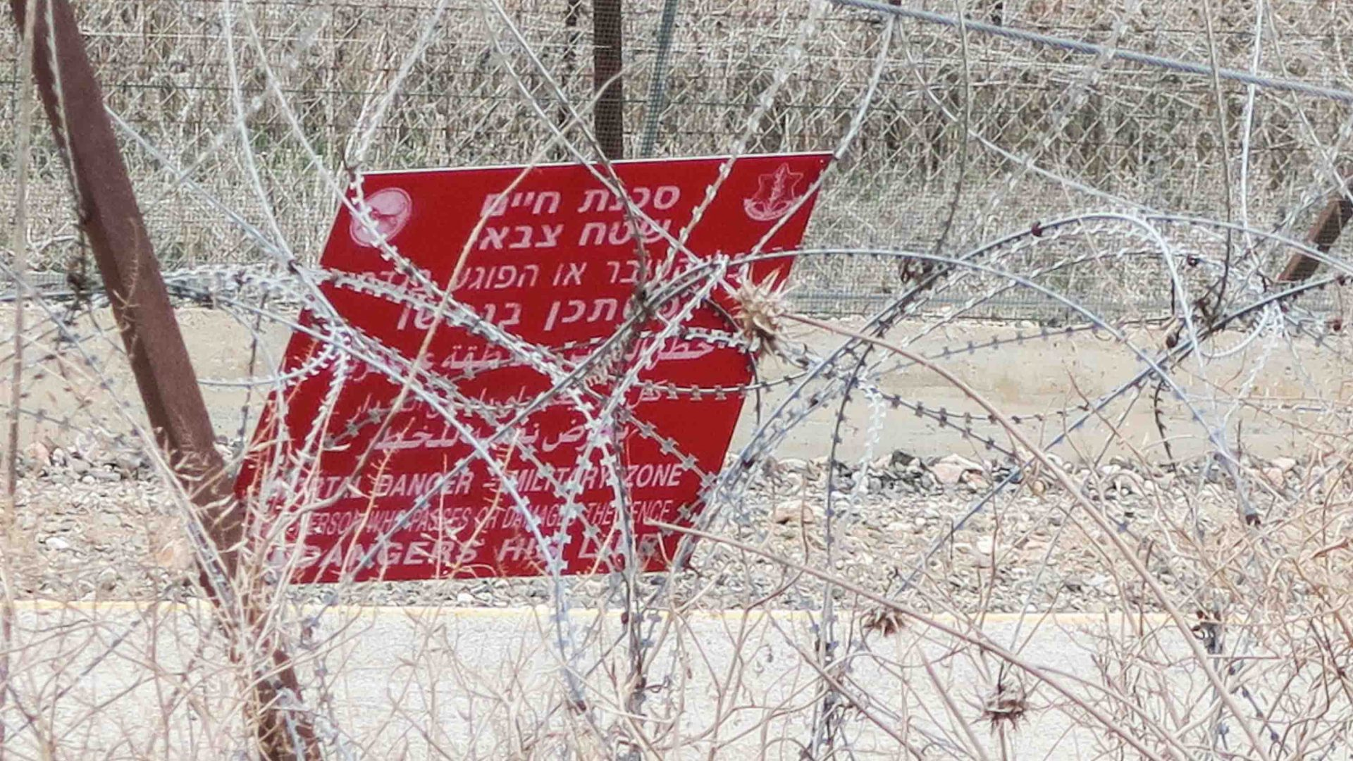 Warning sign in Hebrew, Arabic and English on the separation barrier between Israel and the West Bank.