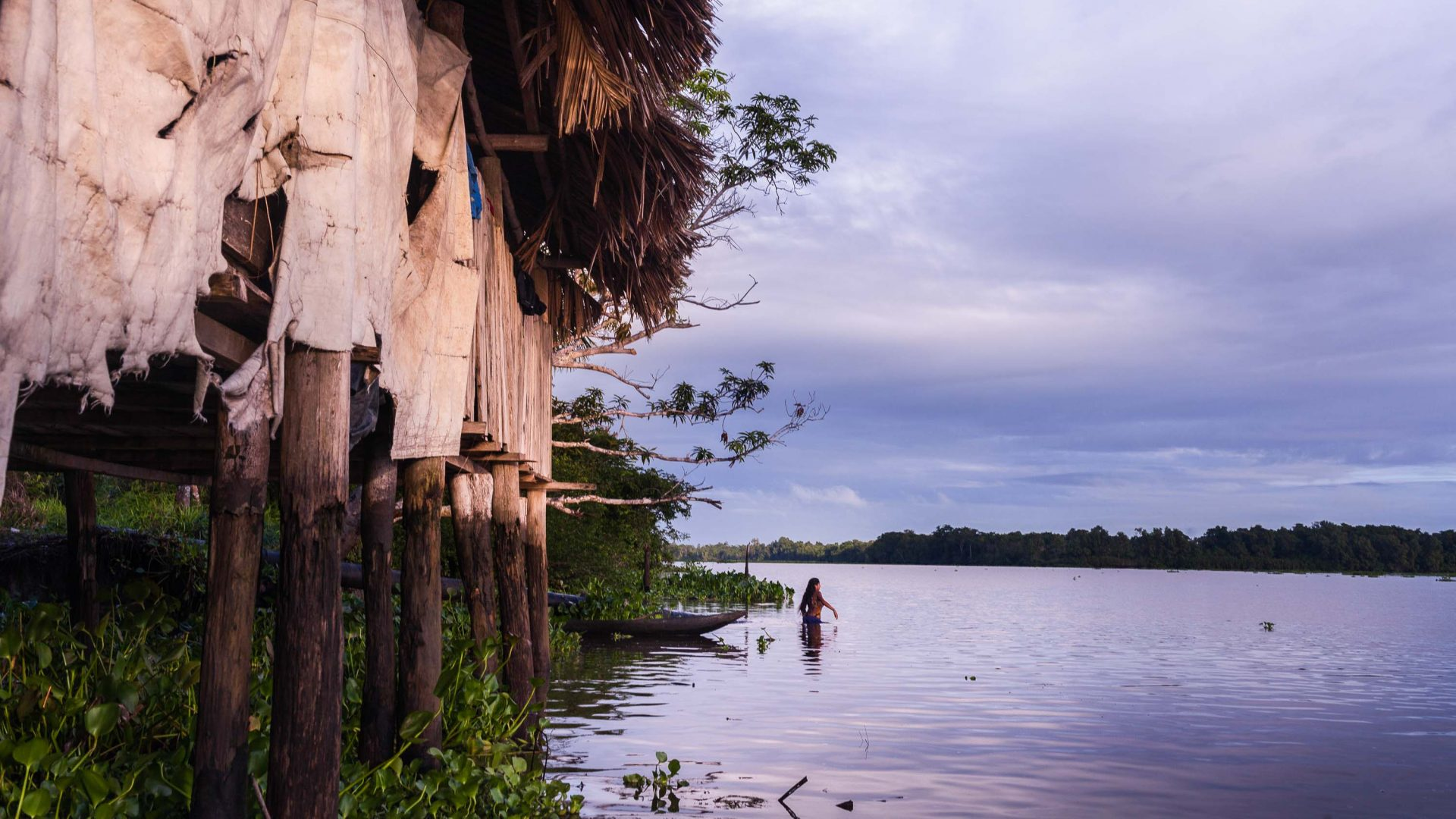 A Warao woman takes a bath at sunrise in the Venezuelan Delta.