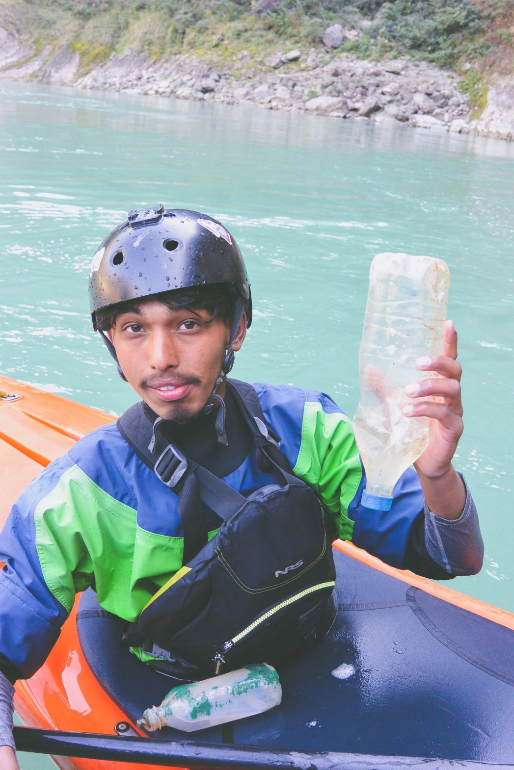 A kayaking guide removes a plastic bottle from the River Ganga in India.