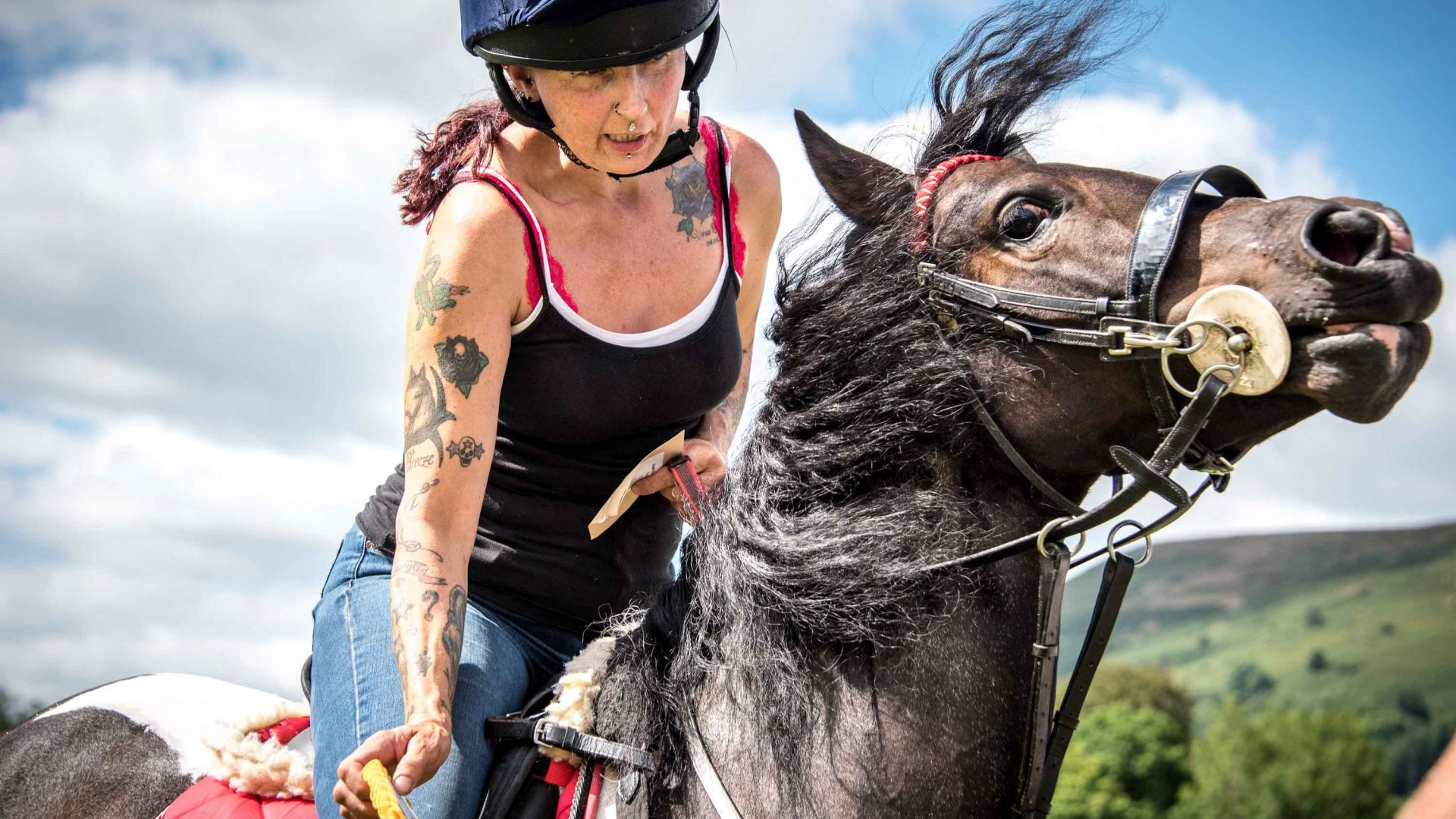 An attendee at the show tries to wrangle the wile horse she is riding.