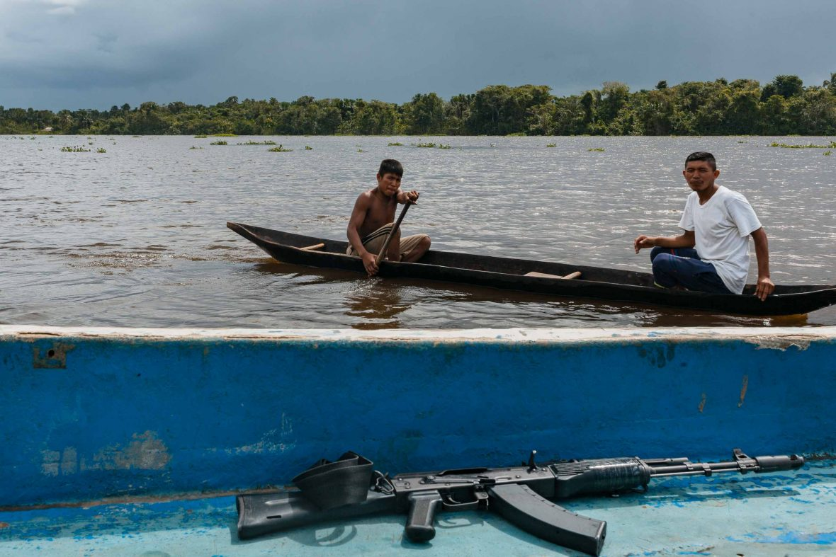 A rifle rests on a boat as the Warao row along Venezuela's Orinoco river. Gasoline and drug traffic have impacted the indigenous community's peaceful traditional living.