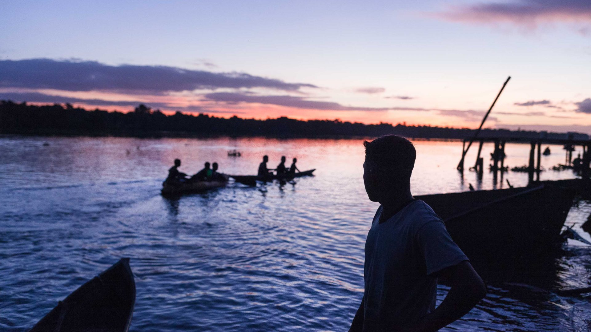 The sun sets as Warao men row back to their homes in the Venezuelan Delta.