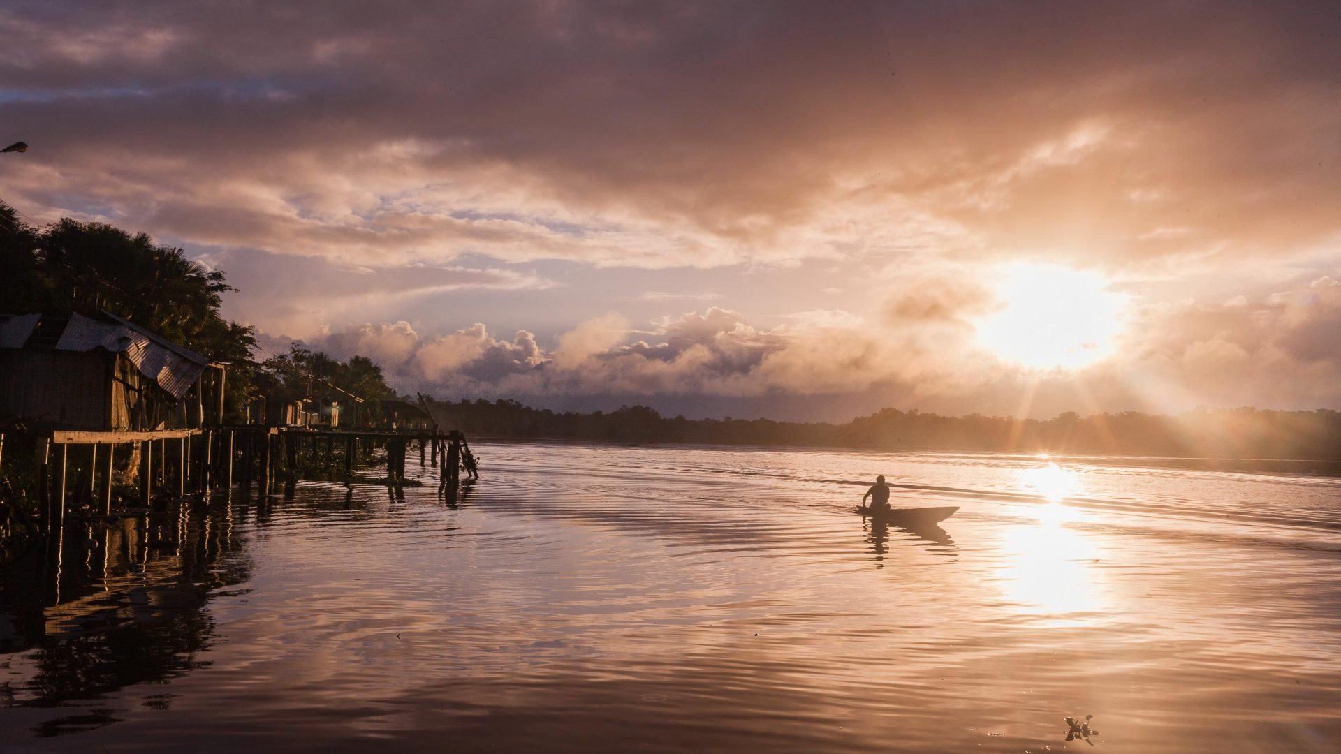 The sun rises as a Warao women rows in the Venezuelan Delta.