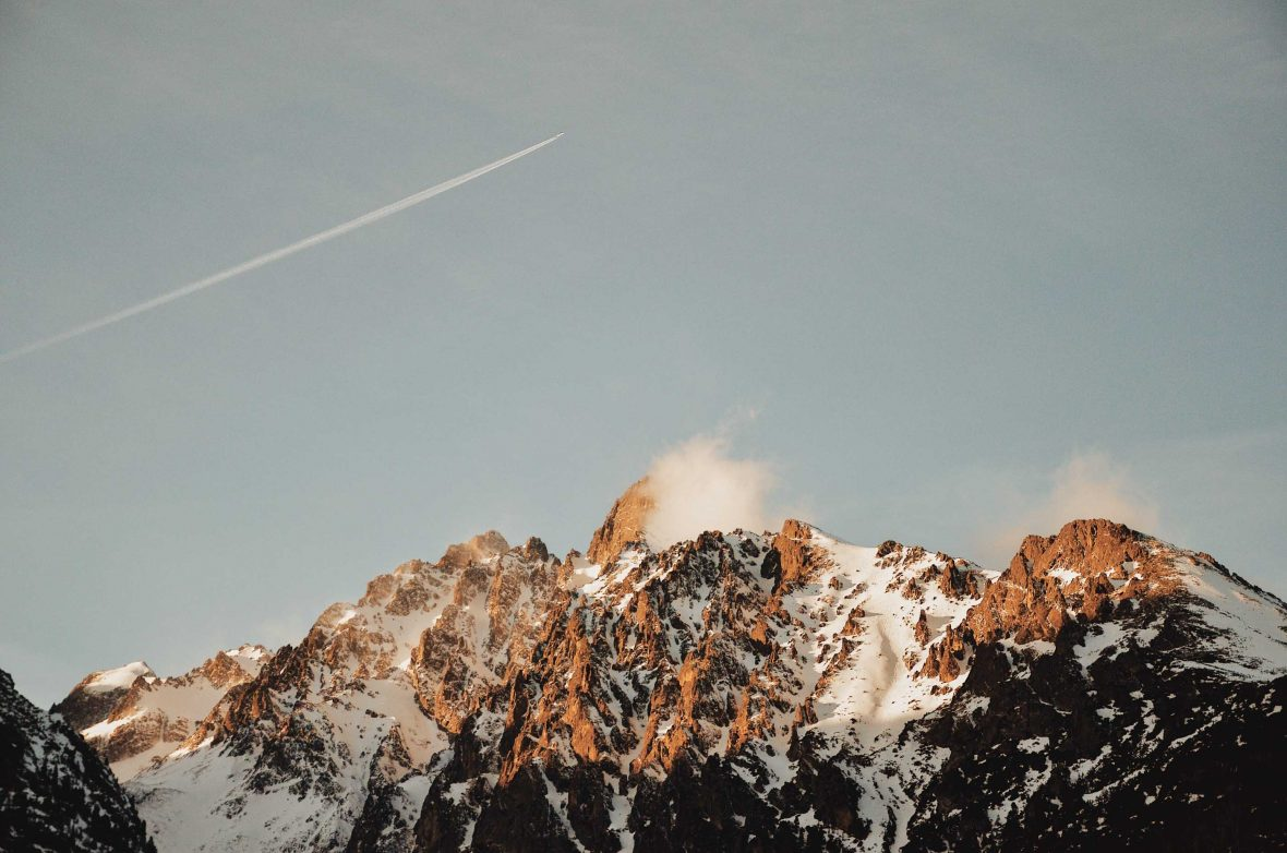 A plane leaves a vapor trail as it flies over wind-blown mountains in Slovakia.