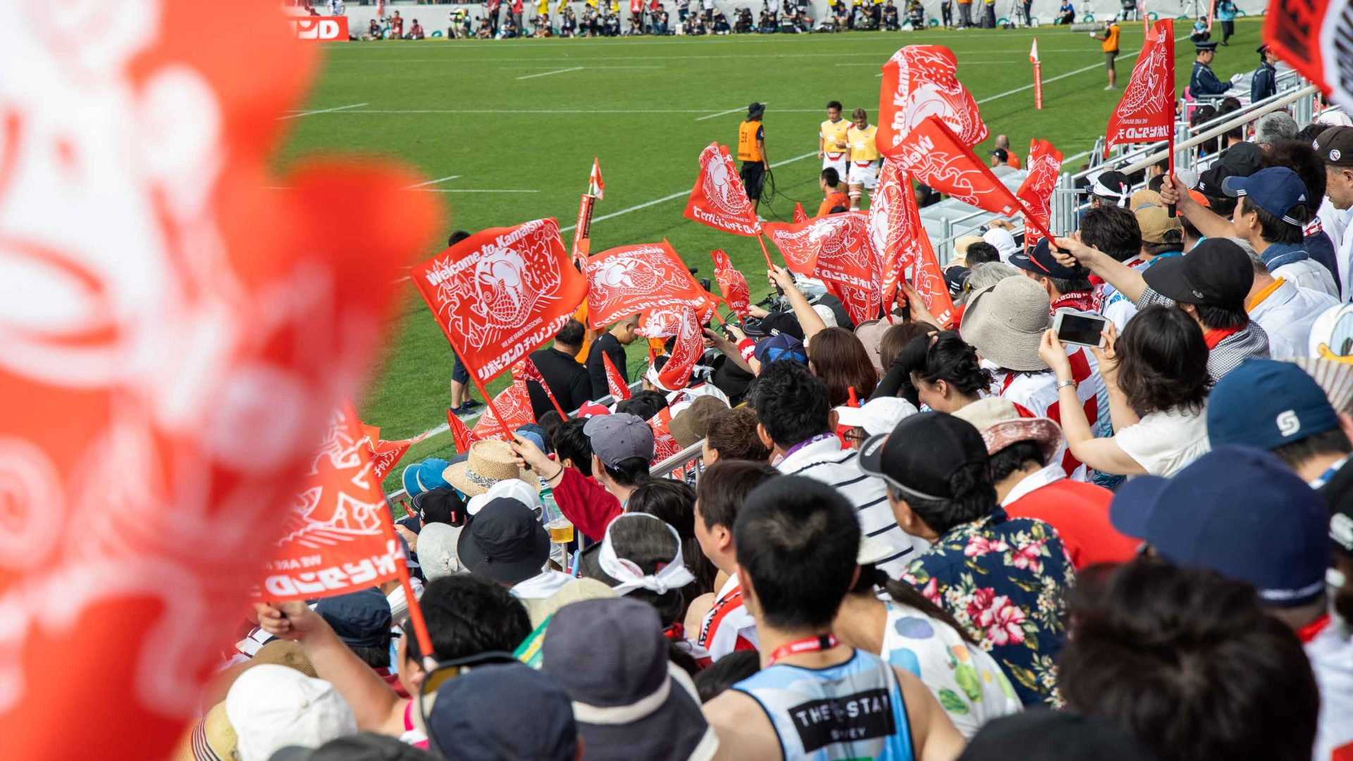 Fans wave flags during the first international match at the Kamaishi Memorial Recovery Stadium, between Japan and Fiji.