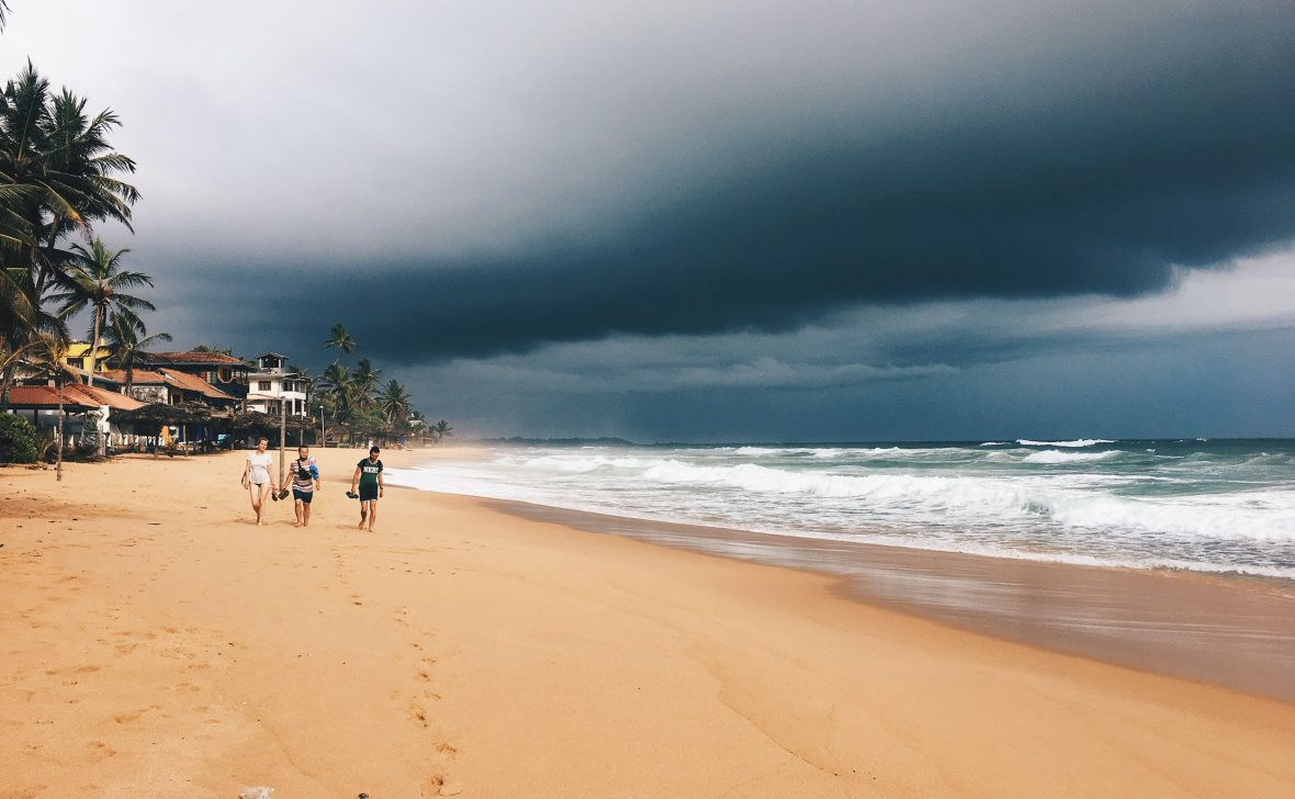 Tourists walk along the beach at Hikkaduwa in Sri Lanka.