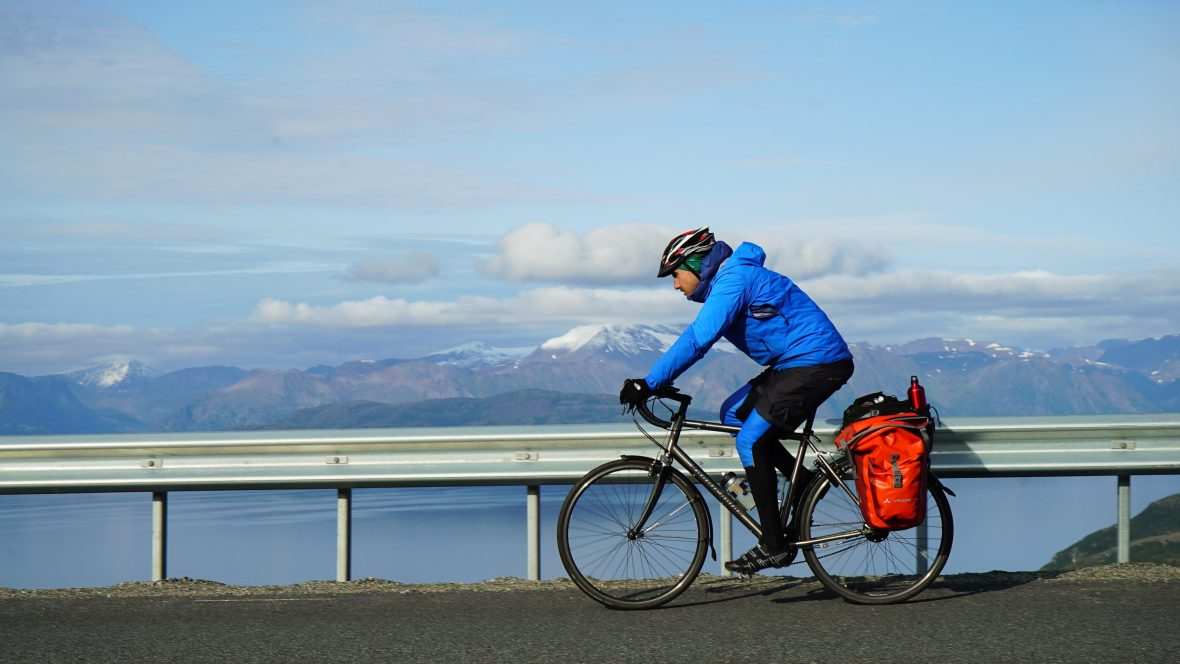 Simon cycling along Lyngen Fjord during his 3,200-kilometer ride across the Scandinavian Peninsula.