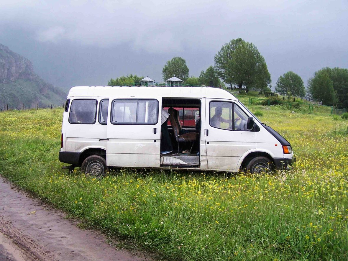 A marshrutka waits in a field by the side of the road.