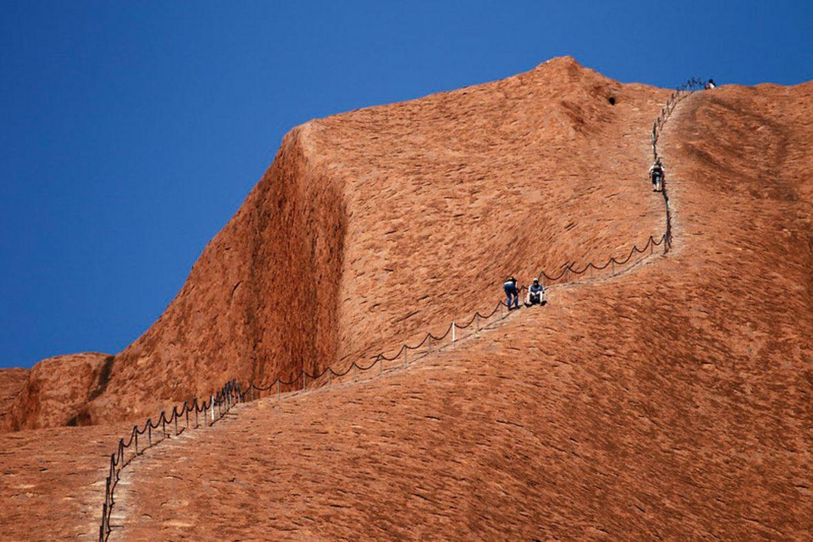People climbing Uluru.