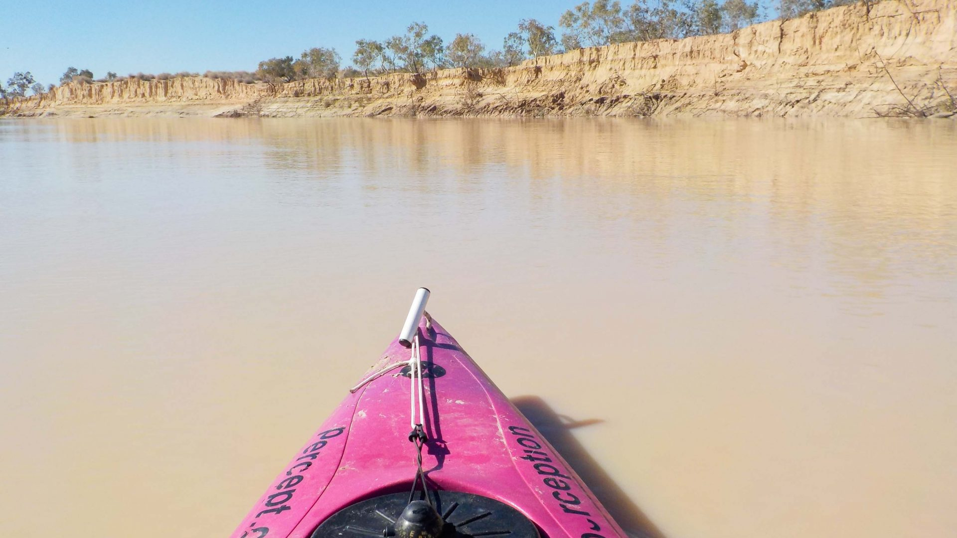 The front of Huy's kayak can be seen, along with the sand cliffs along the Warburton River in South Australia.