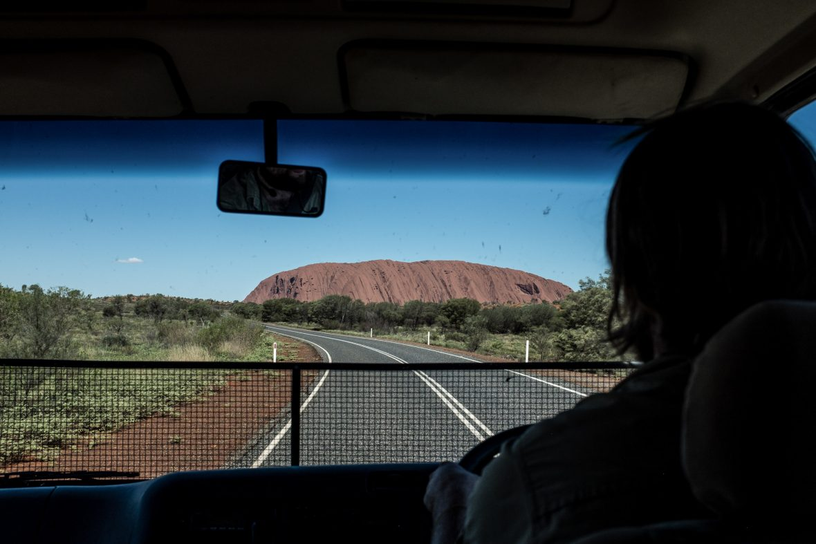 Justin driving with Uluru in the background.