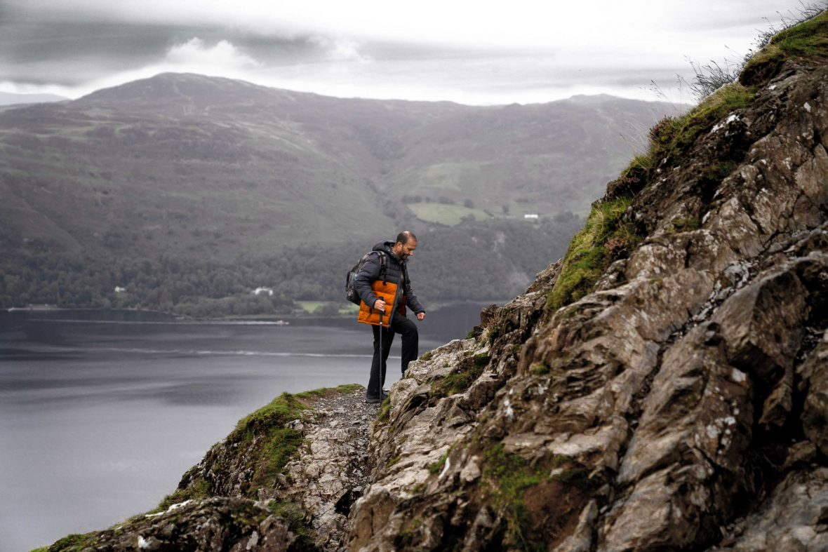 One of the members of Boots and Beards climbs a rocky cliff face in Lake District National Park.