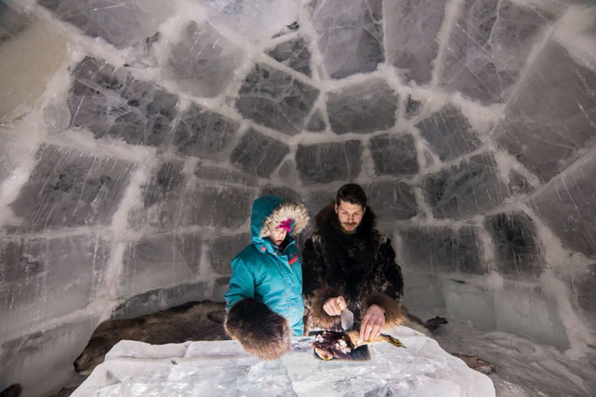 Tourists to Canada's Northwest Territories can sleep in an igloo as part of the experience, as well as seeing reindeer. Here, some travelers cut meat inside an igloo.