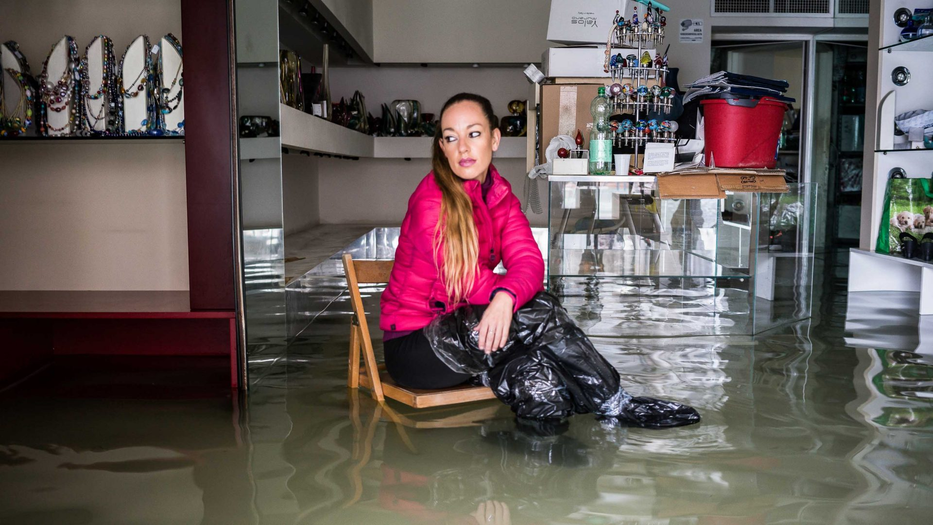 A woman surrounded by flood waters sits in her shop in Venice.