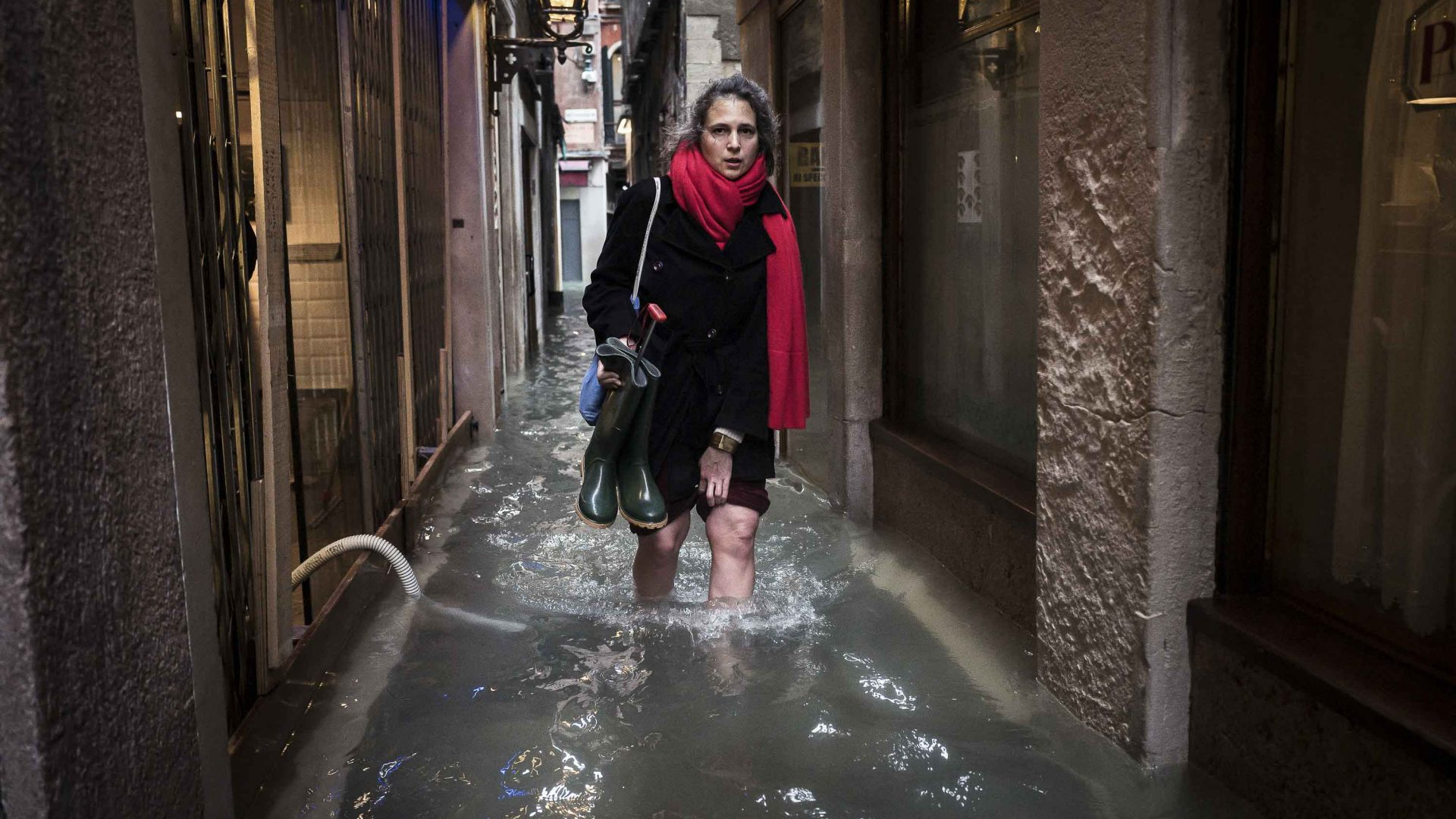A woman walks through the flooded streets of Venice.